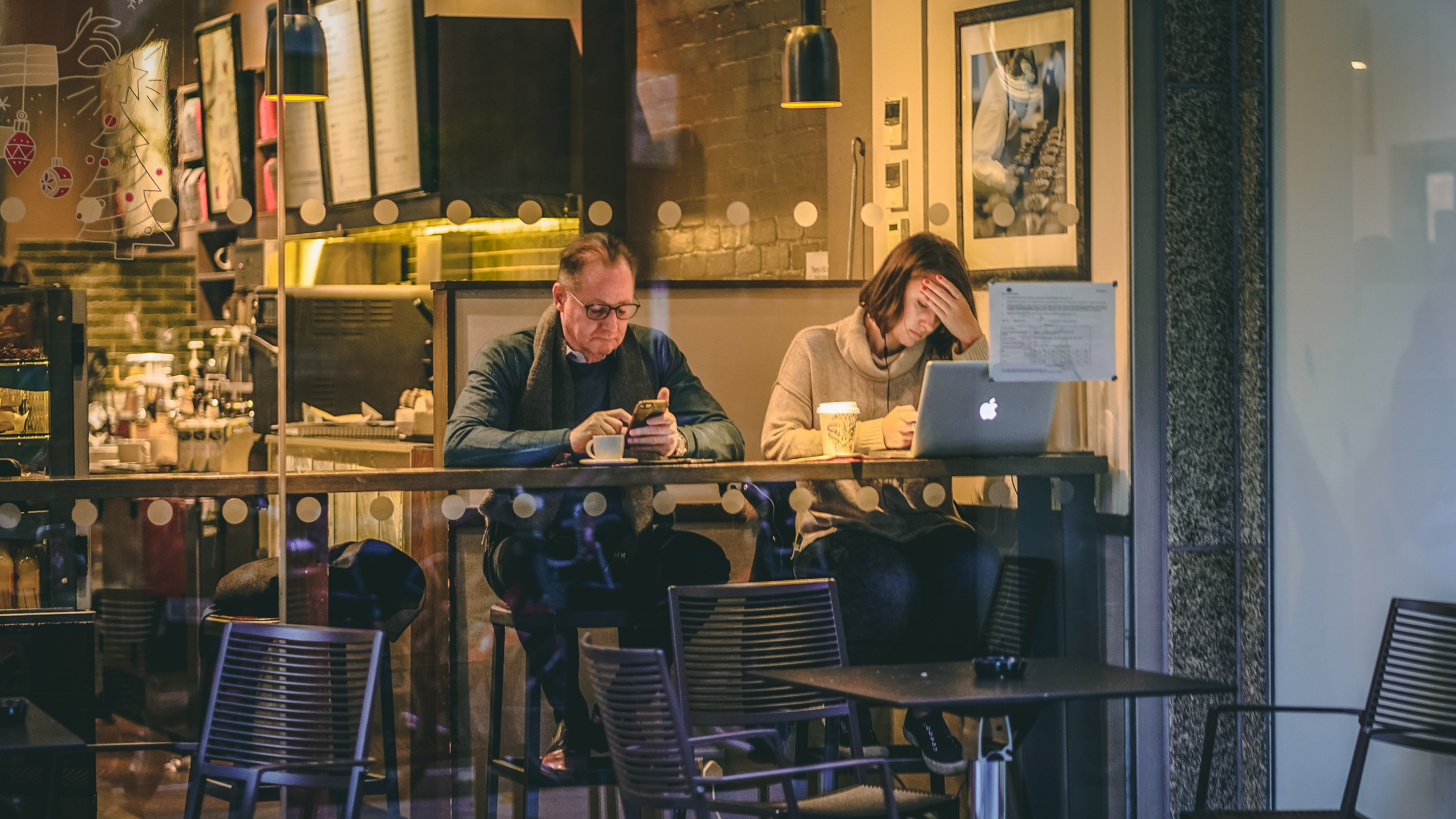 man holding smartphone sitting beside woman in front of silver MacBook in restaurant