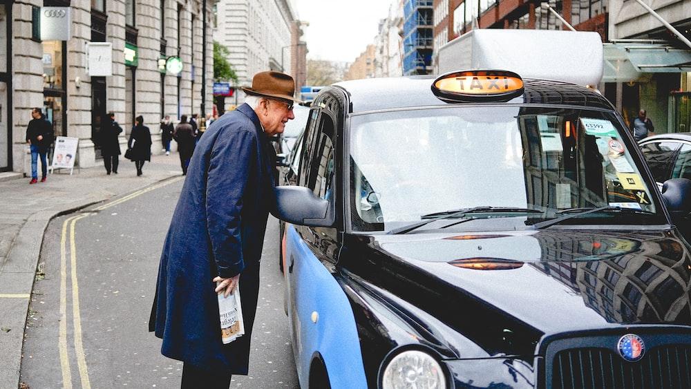 man talking through taxi car mirror during daytime