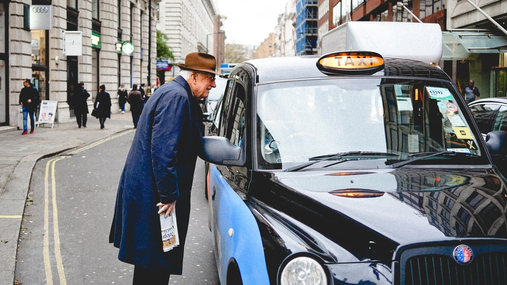 man talking through taxi car mirror during daytime