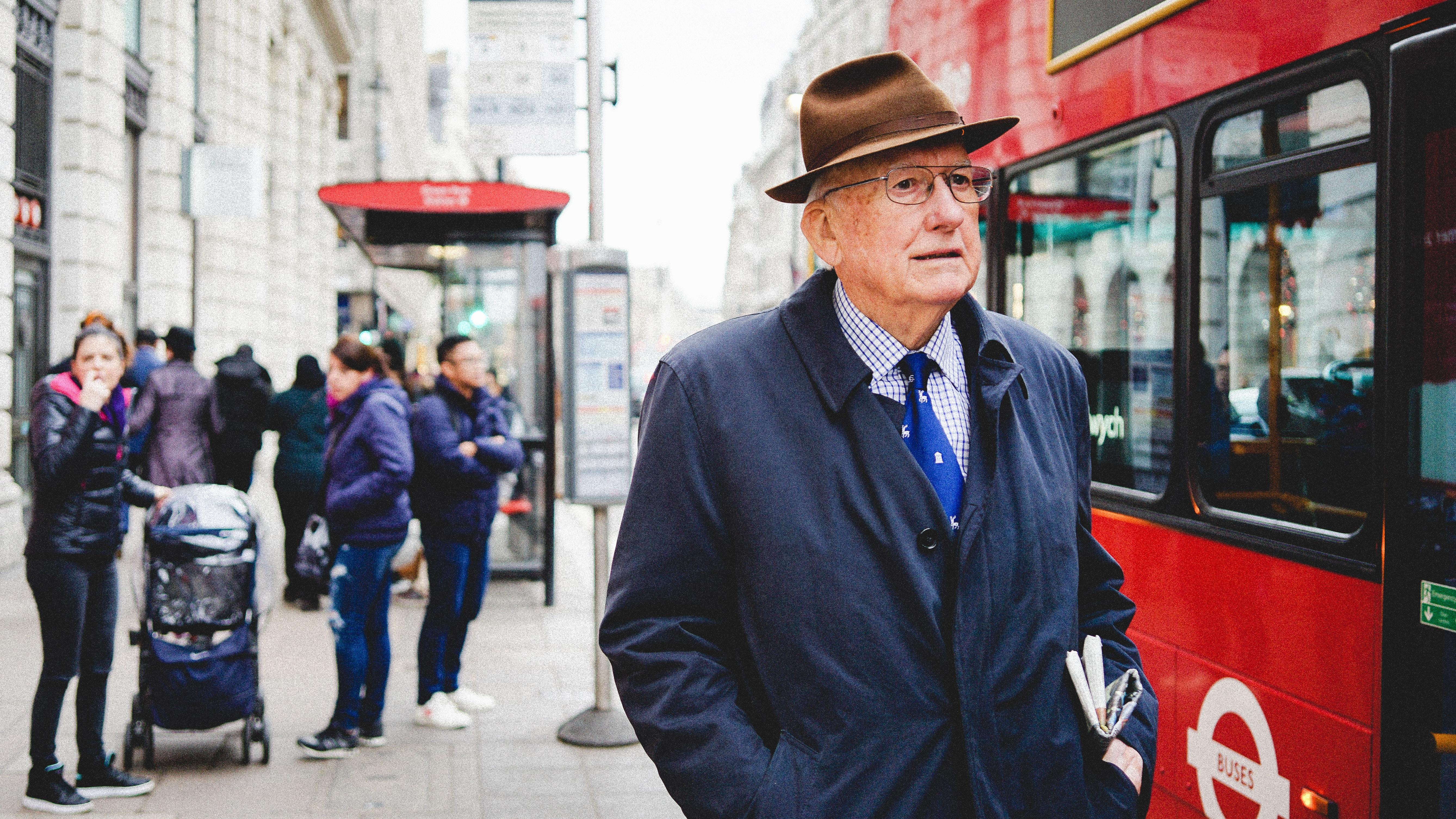man standing near red bus at daytime