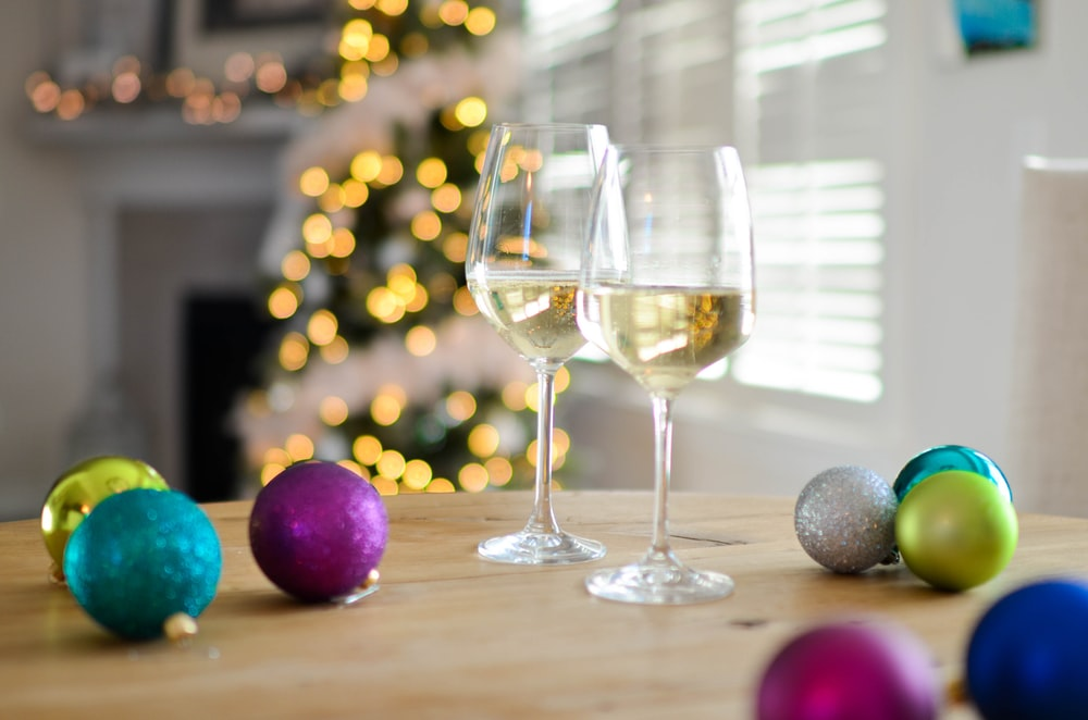 two clear footed wineglasses filled with yellow liquid near assorted-color ball ornaments