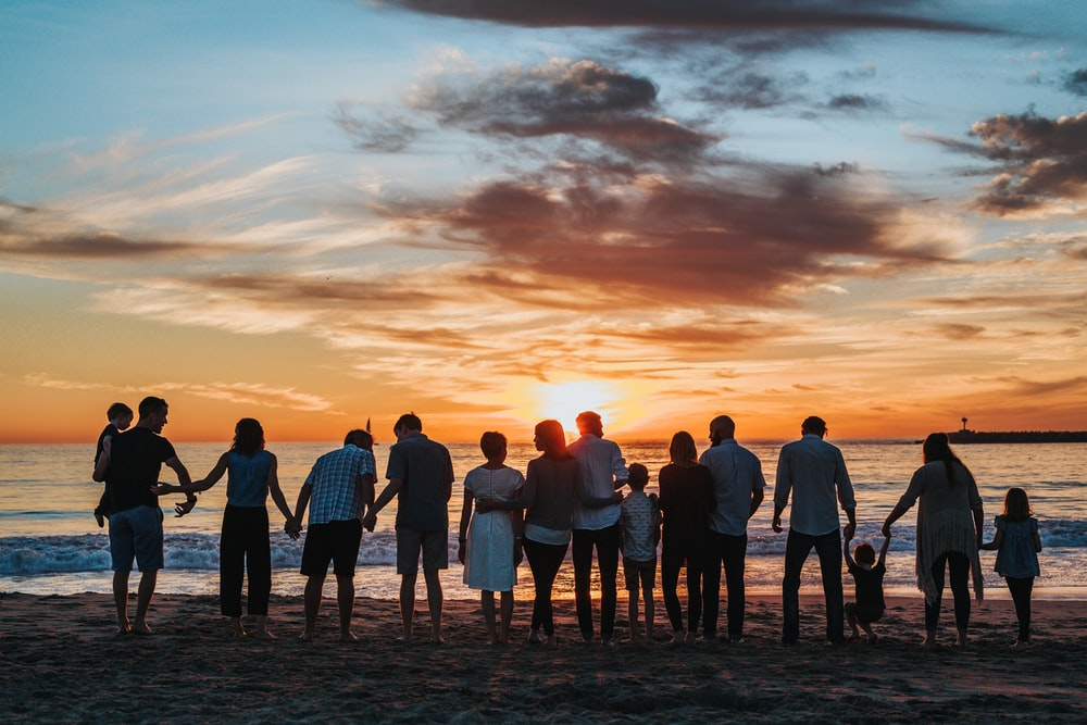 people standing on shore during golden hour