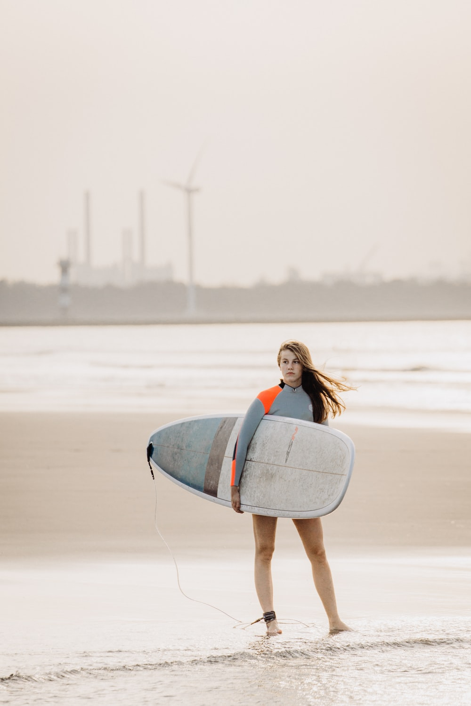 woman standing on seashore carrying surfboard
