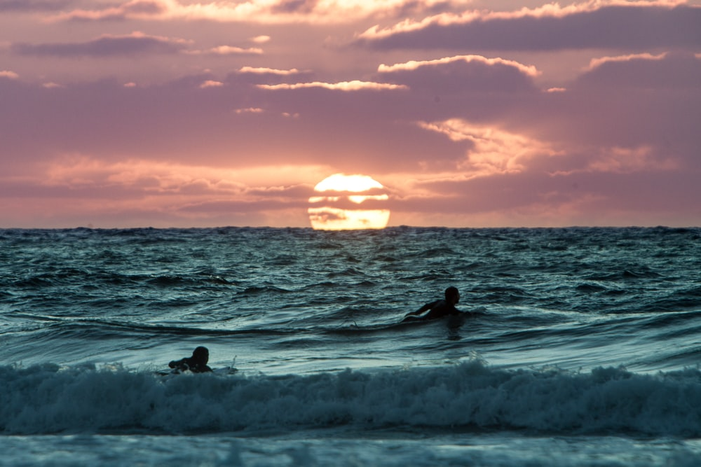 two person swimming on body of water during golden hour