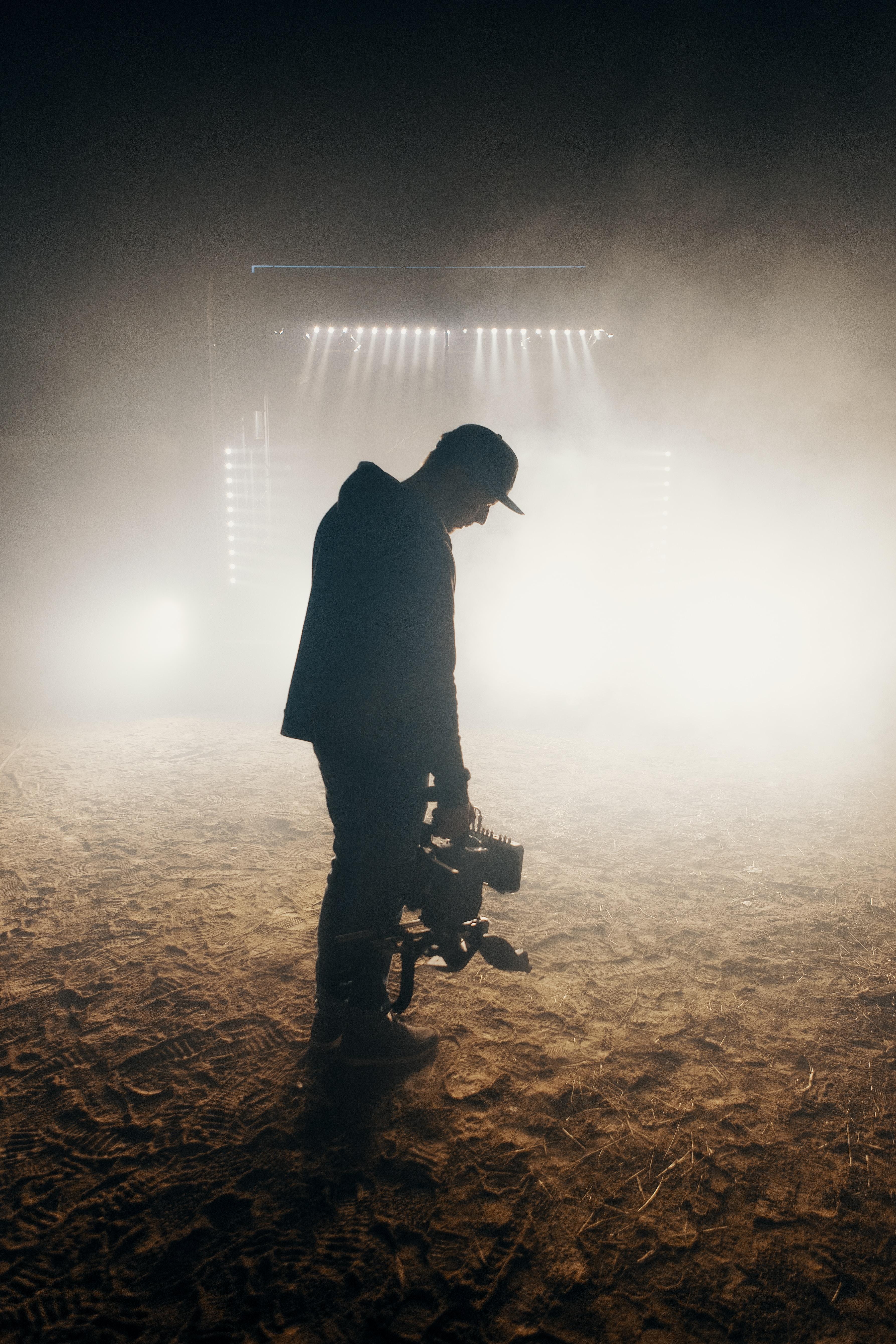 man standing on brown soil wearing cap