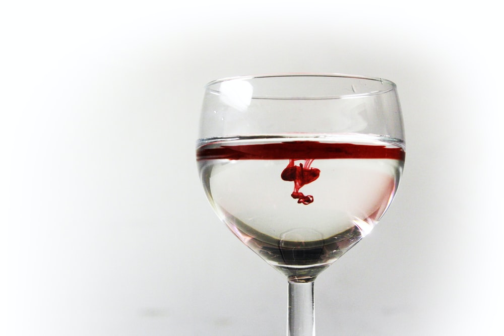 clear wine glass filled with red liquid