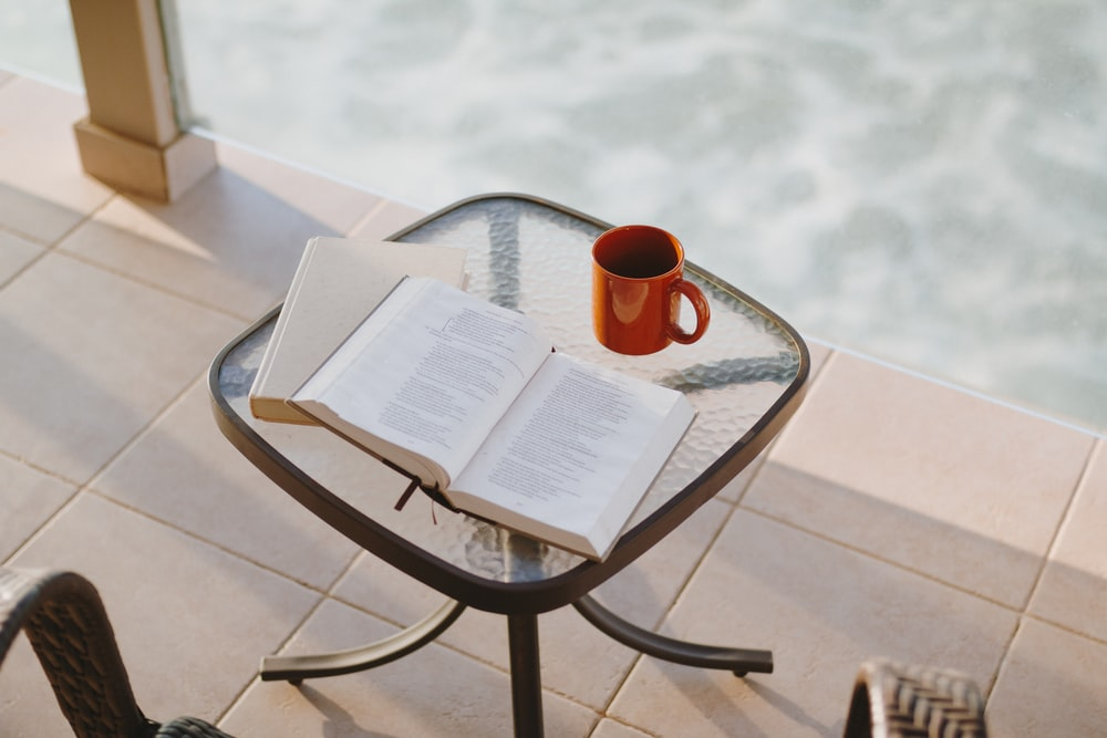 book beside mug on square clear glass-top table