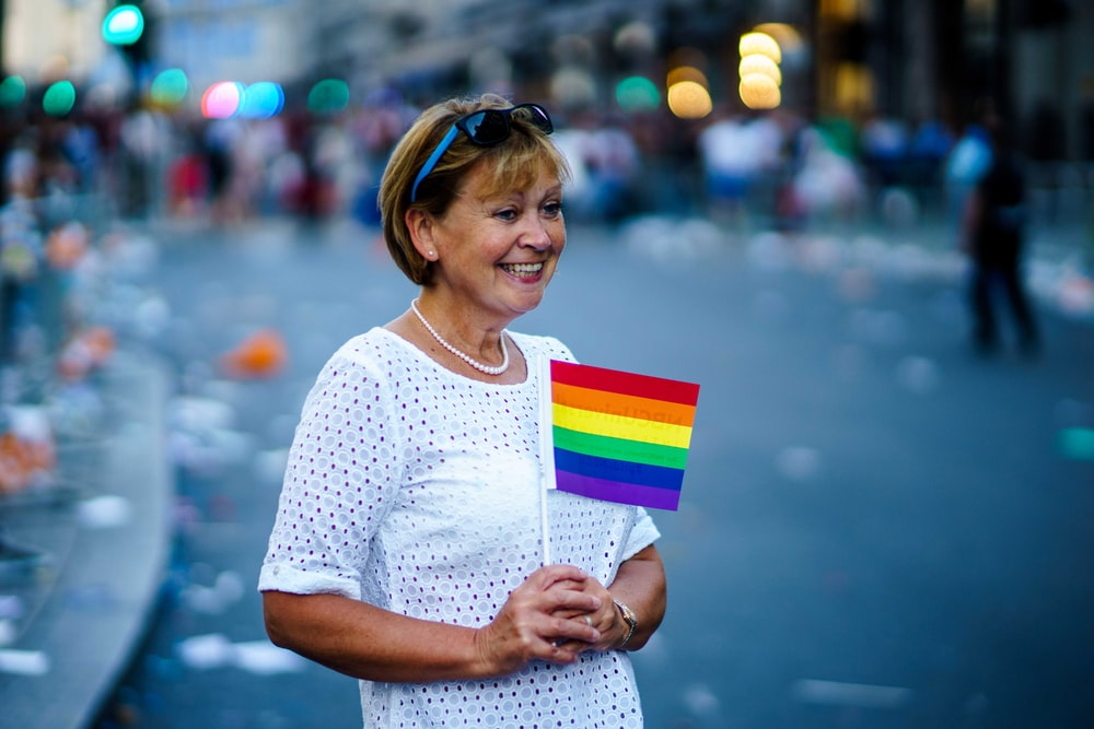 woman smiling holding LGBT flaglet