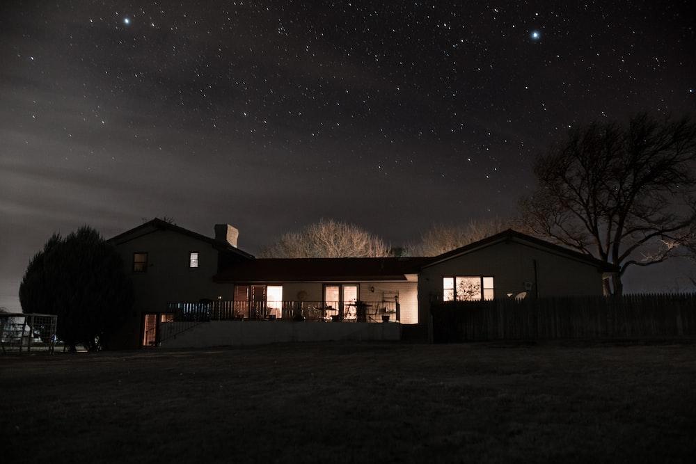 landscape photography of a house under nightsky