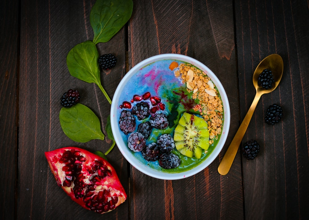 mixed fruits on bowl with blueberry on top