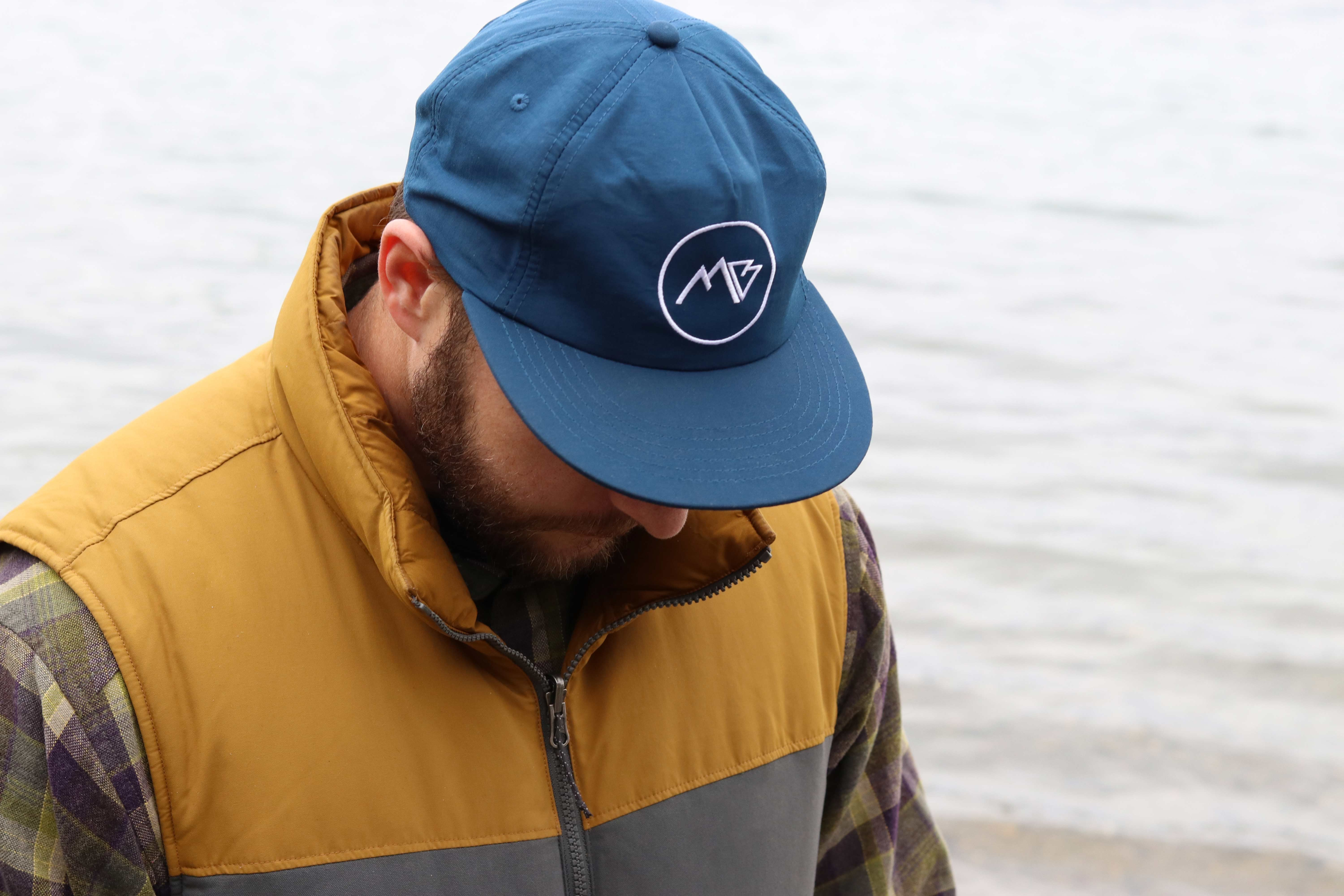 man wearing vest and cap looking down beside body of water