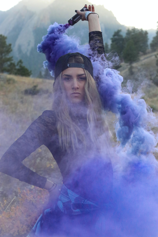 woman raising purple smoke bomb during daytime