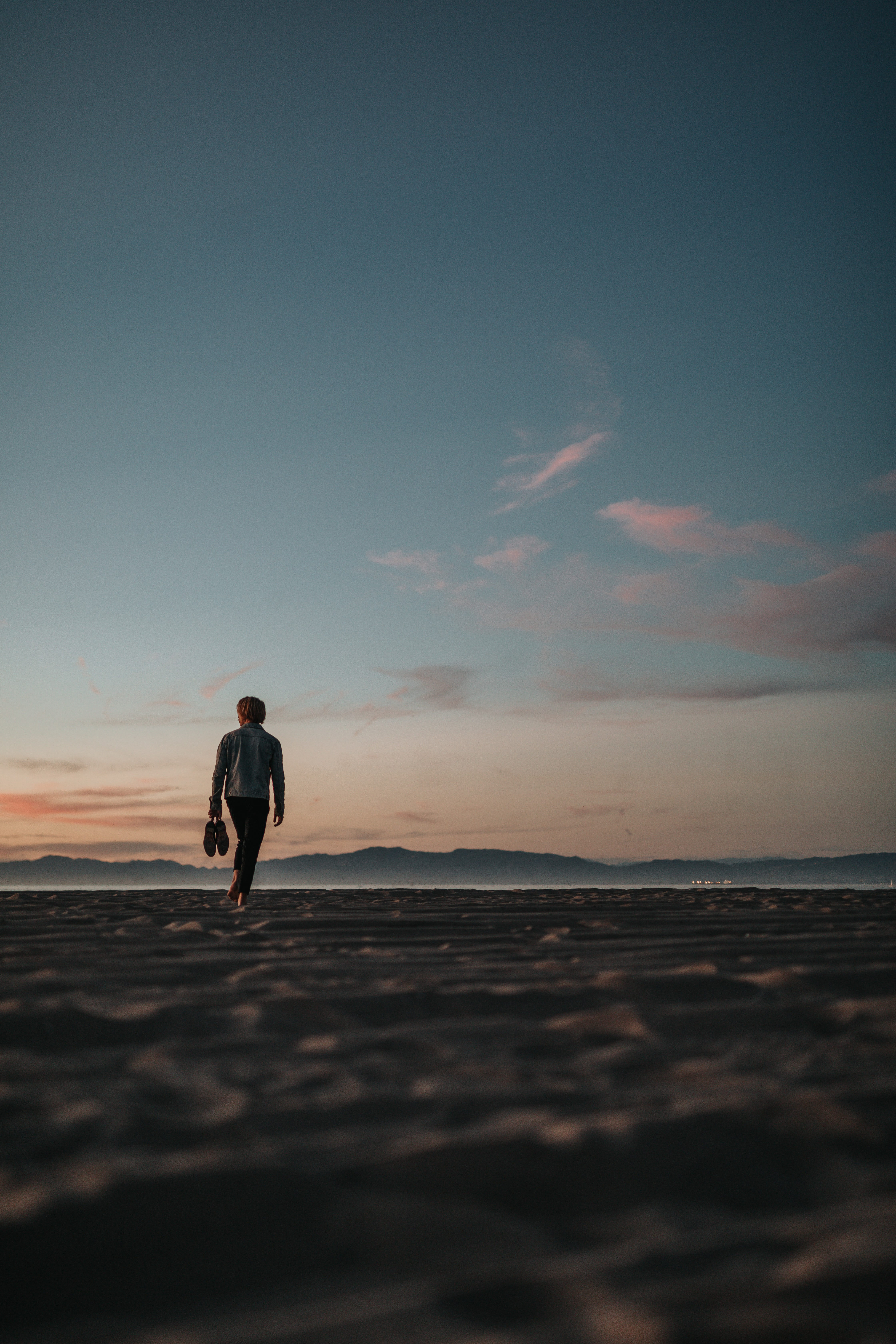 man walking on sand while holding his footwears