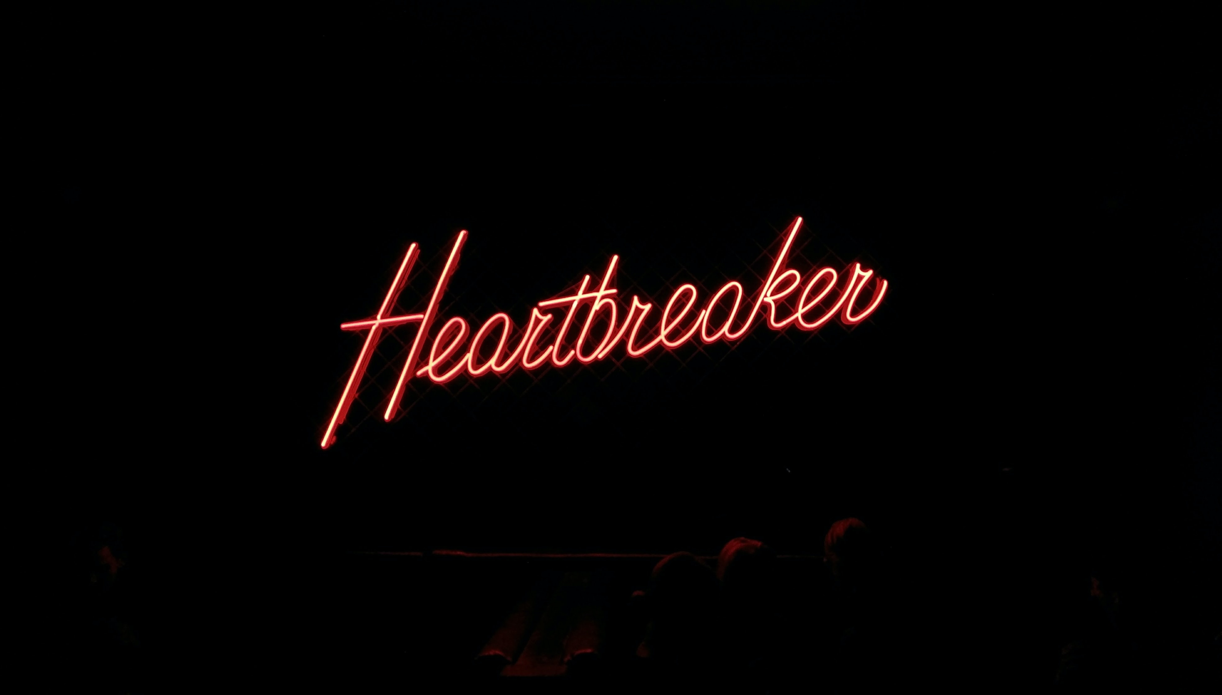 Heartbreaker neon signage on black background