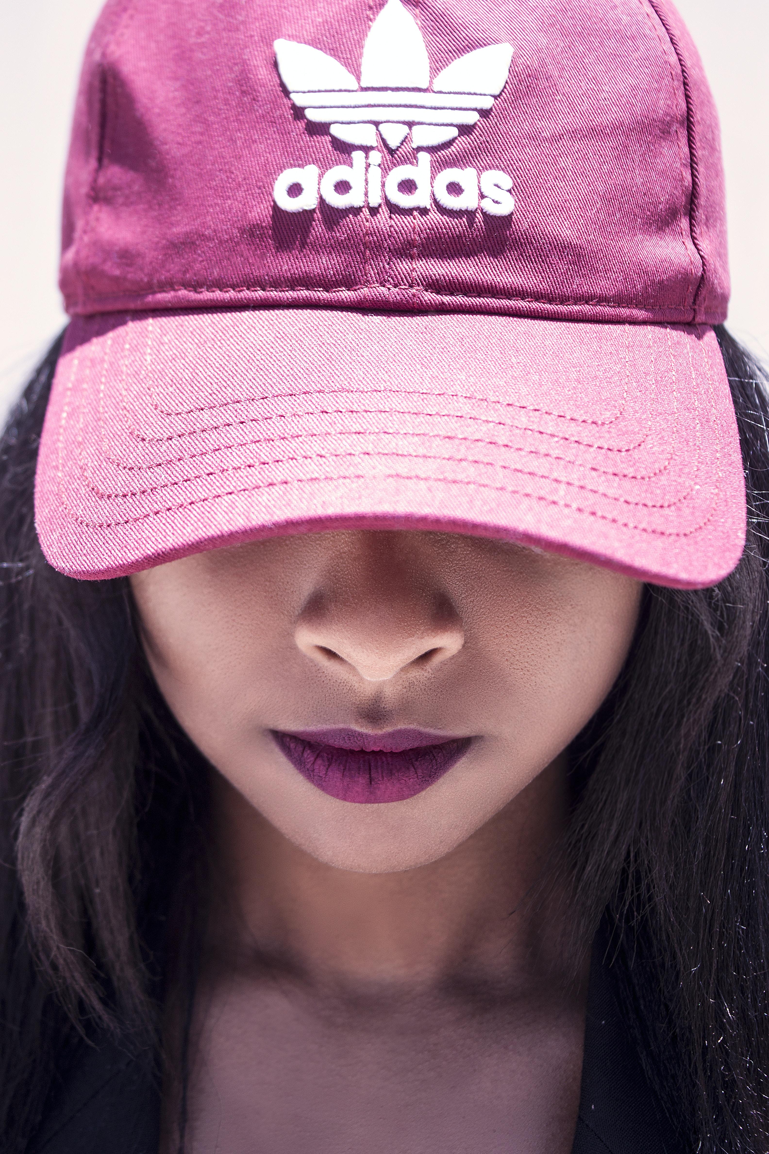 woman wearing pink adidas baseball cap