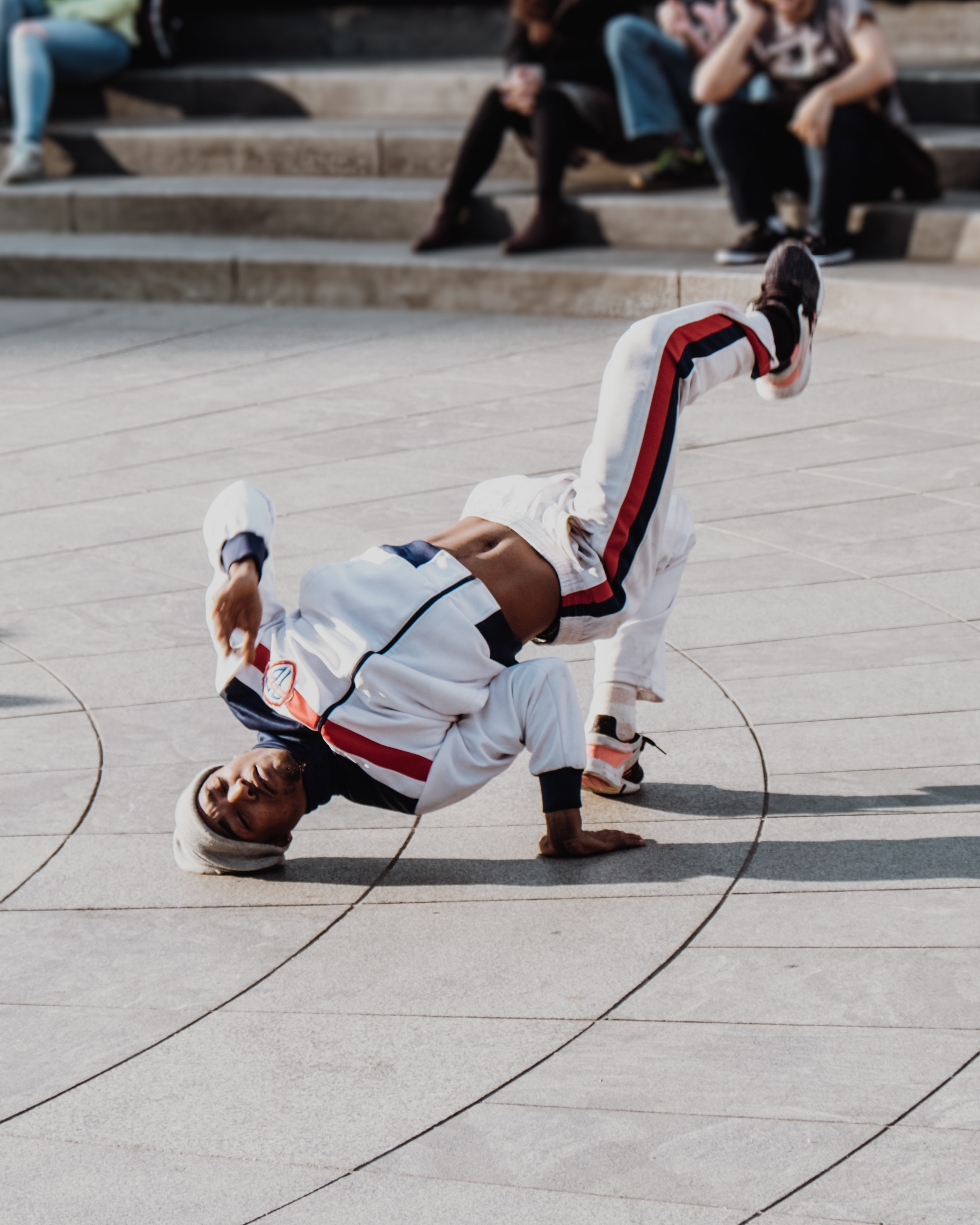 man doing bboy in front of people at daytime