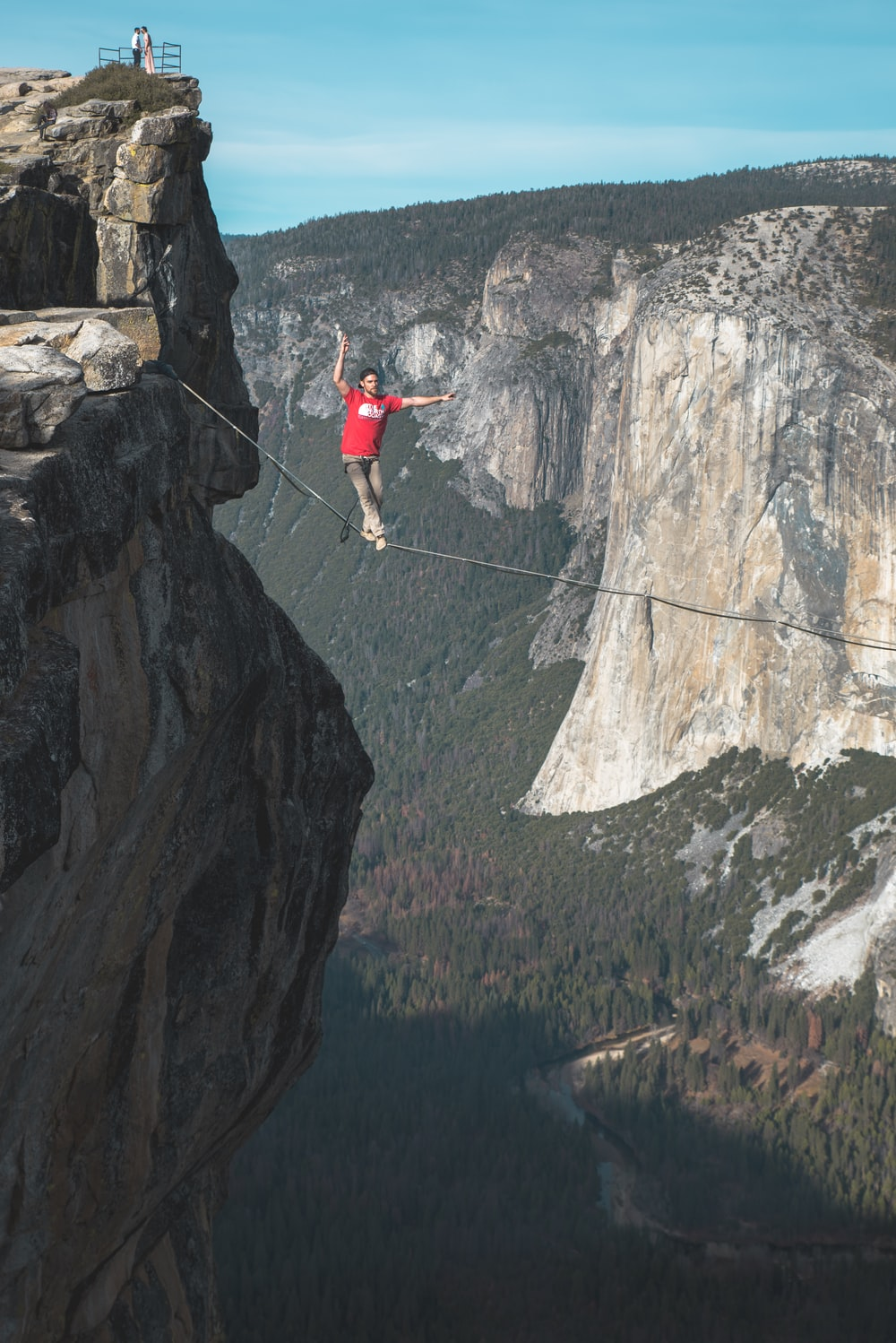 person standing on rope near mountain cliff
