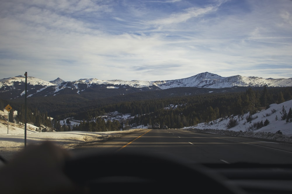 gray concrete road overviewing snow caped mountain