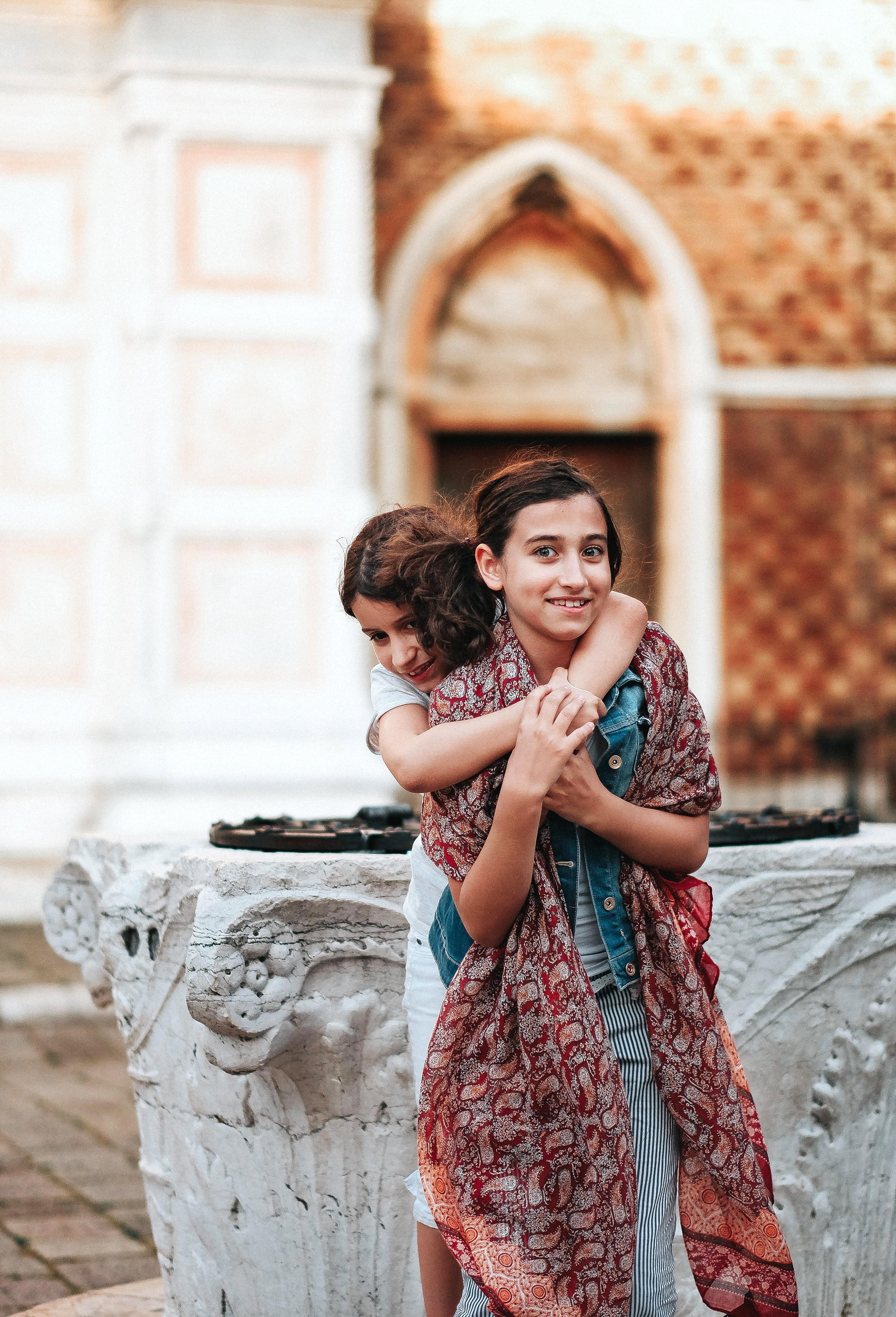 girl hugging girl wearing maroon scarf