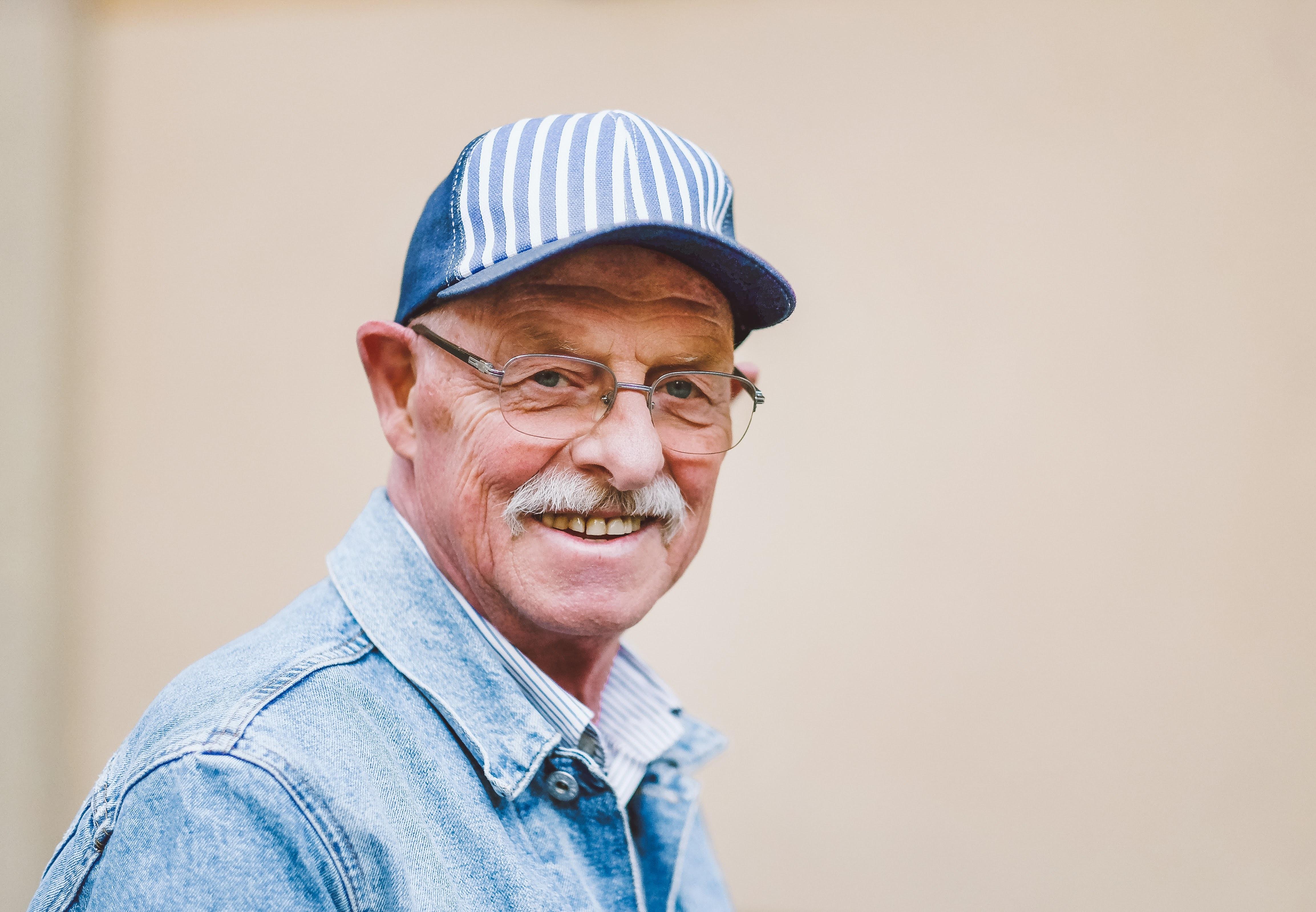smiling man wearing blue denim collared top