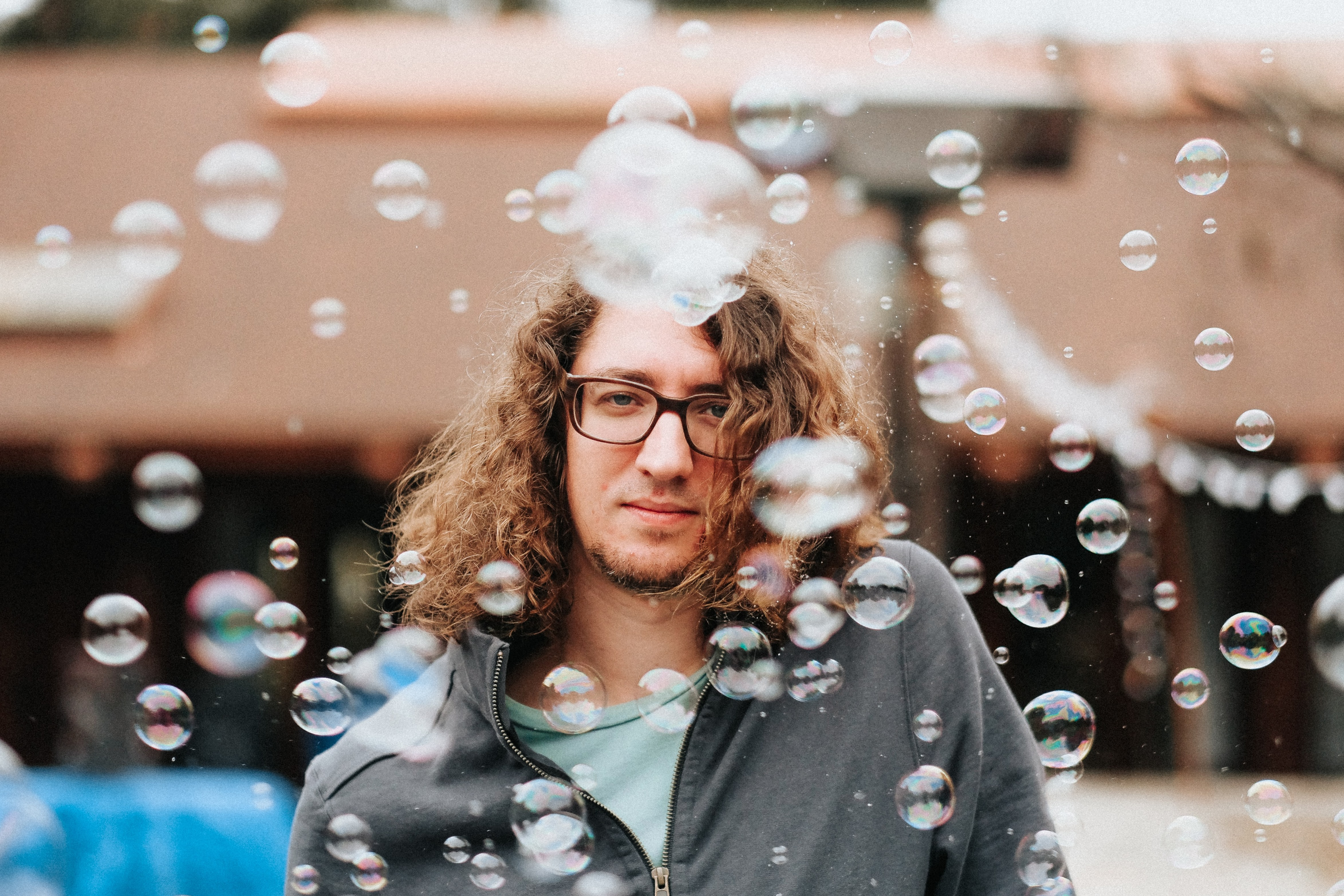 man standing while surrounded by bubbles