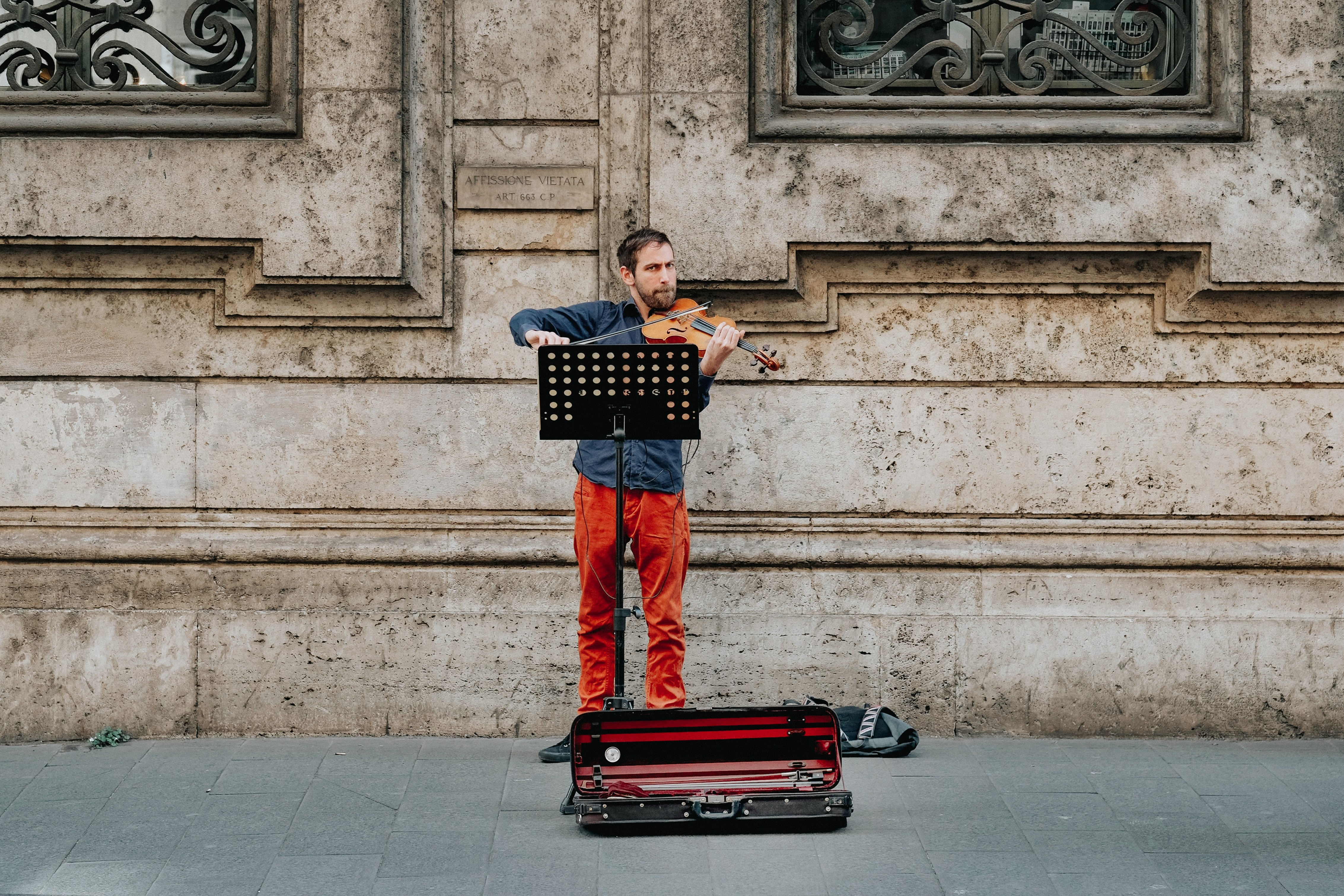 man playing brown violin near building at daytime