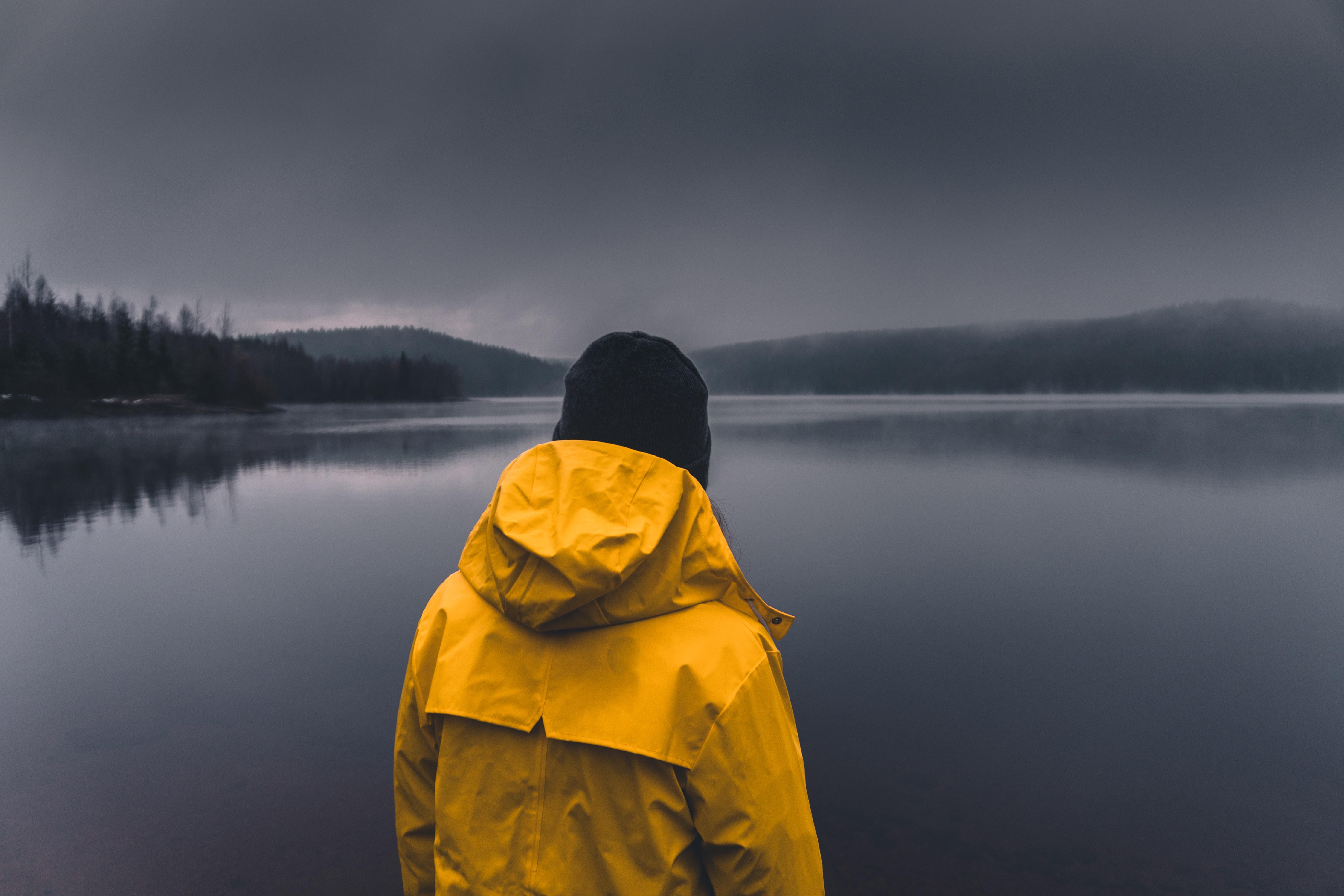 man facing calm body of water under cloudy sky