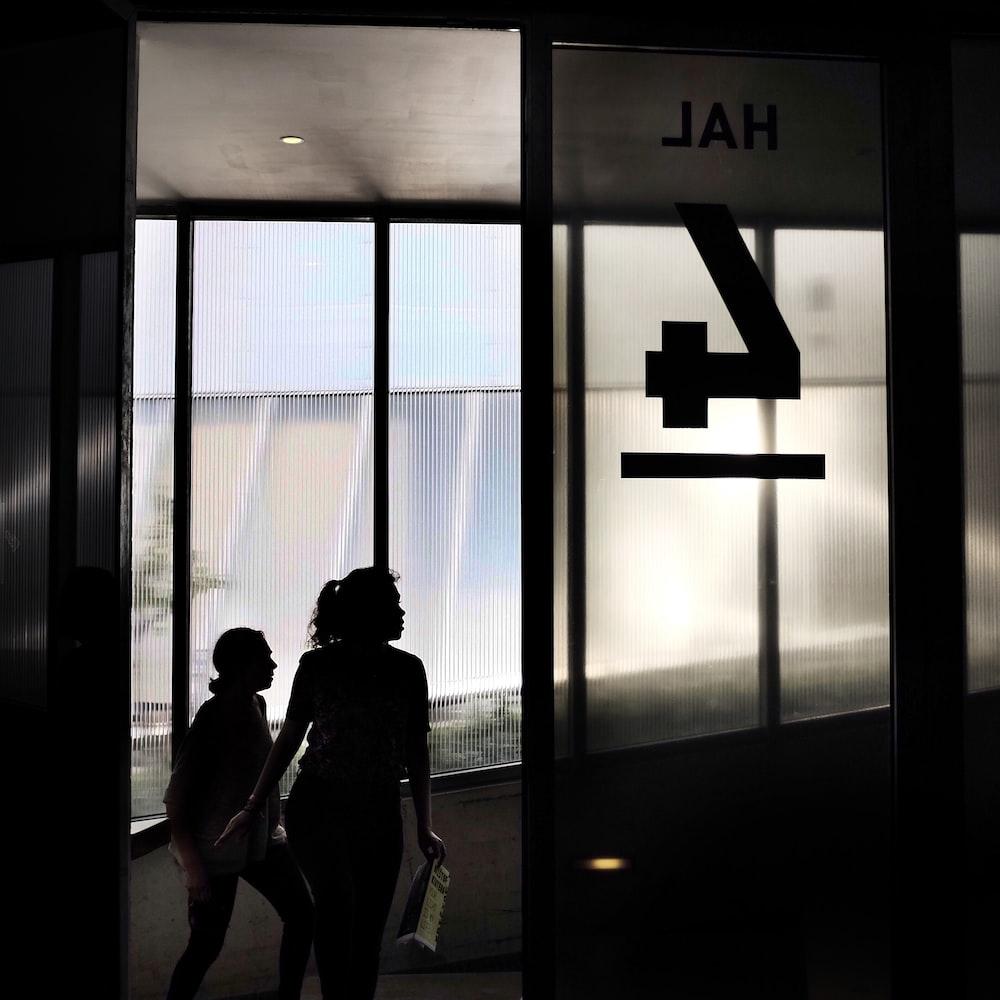 two woman walking through door