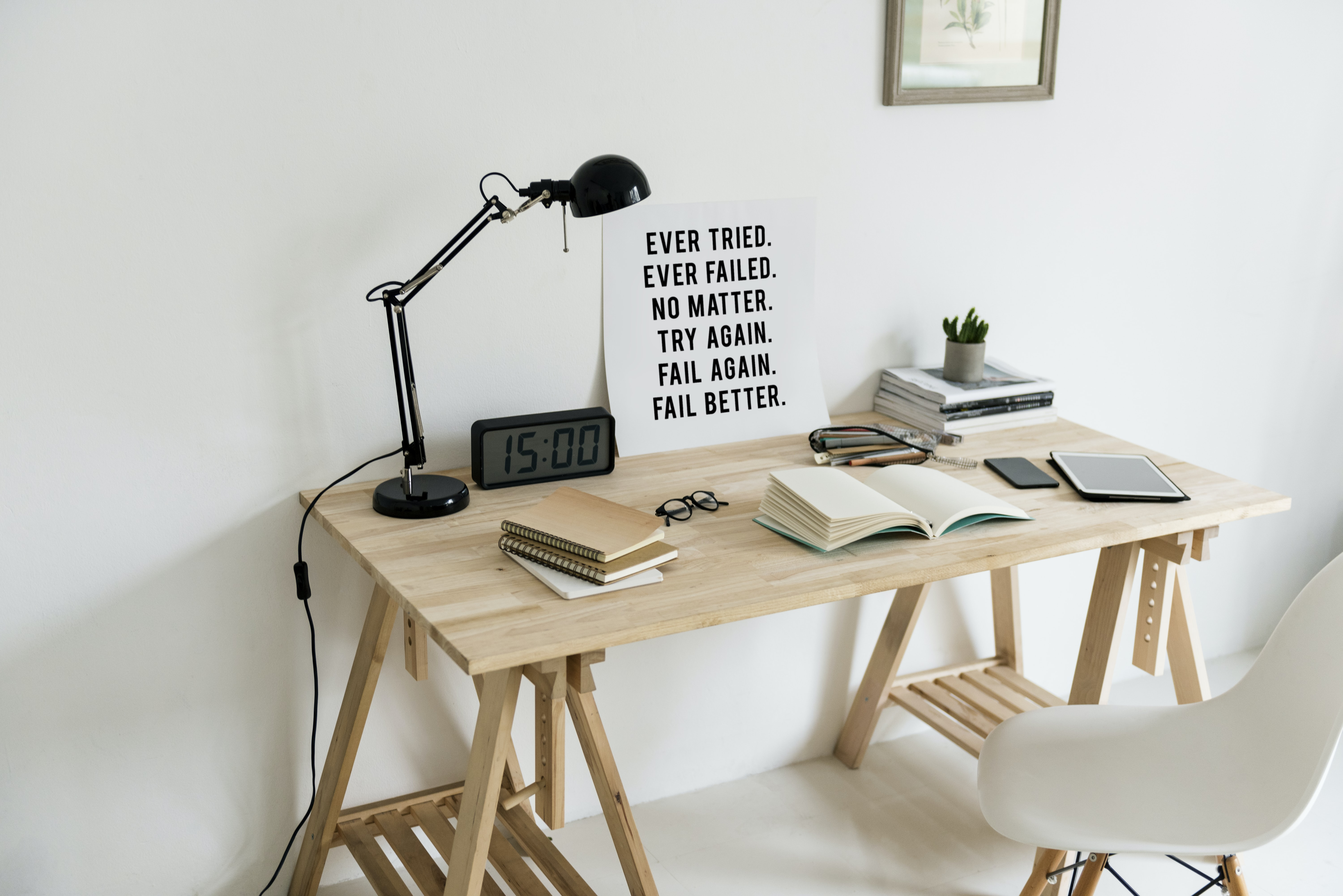 wooden desk with books and task lamp