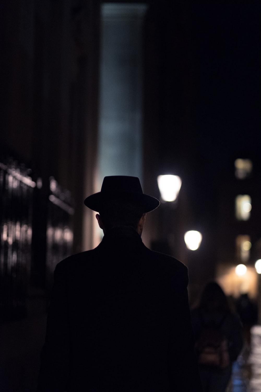 man in black hat walking on sidewalk during night time