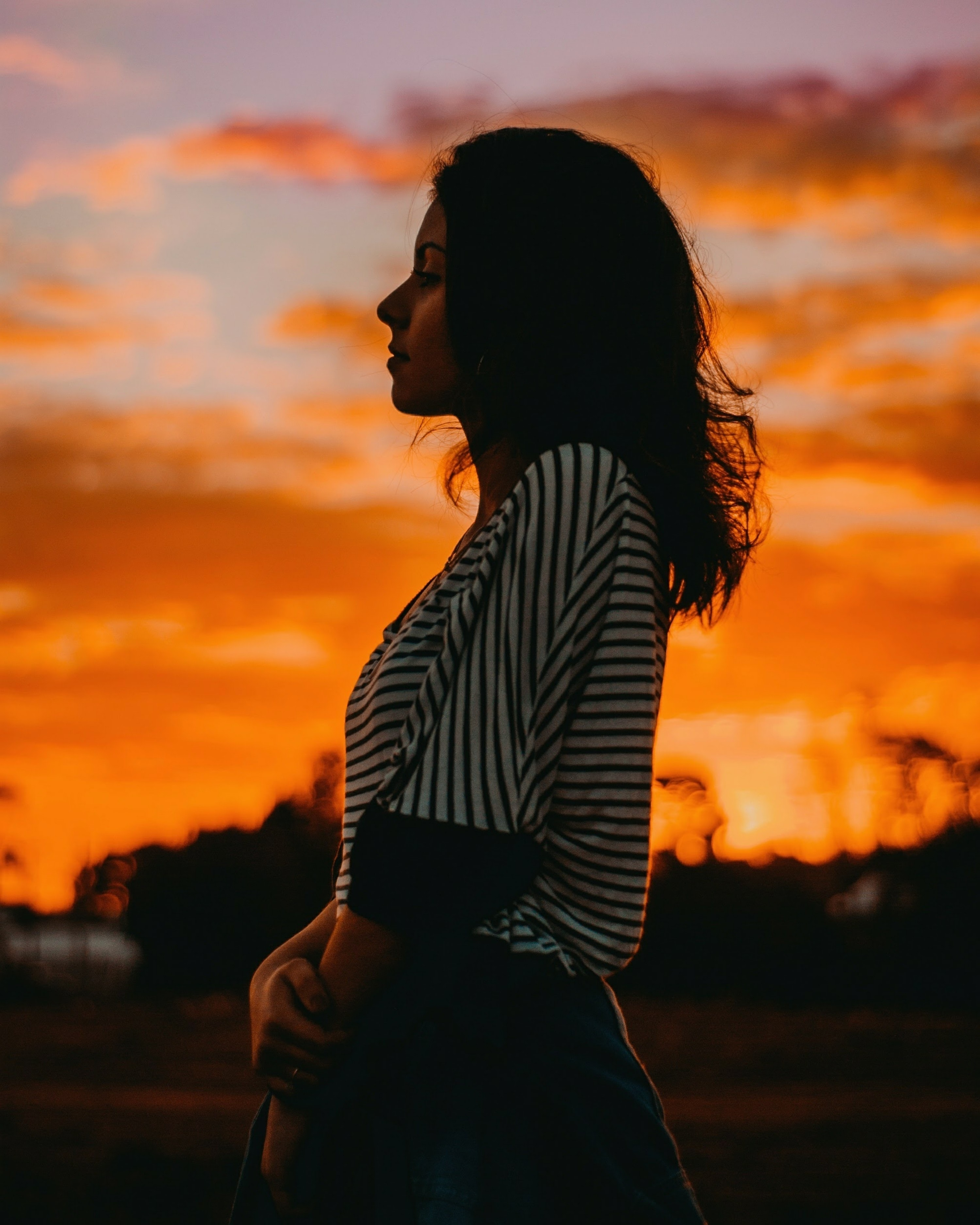 woman in black and white striped top standing outside during sunet