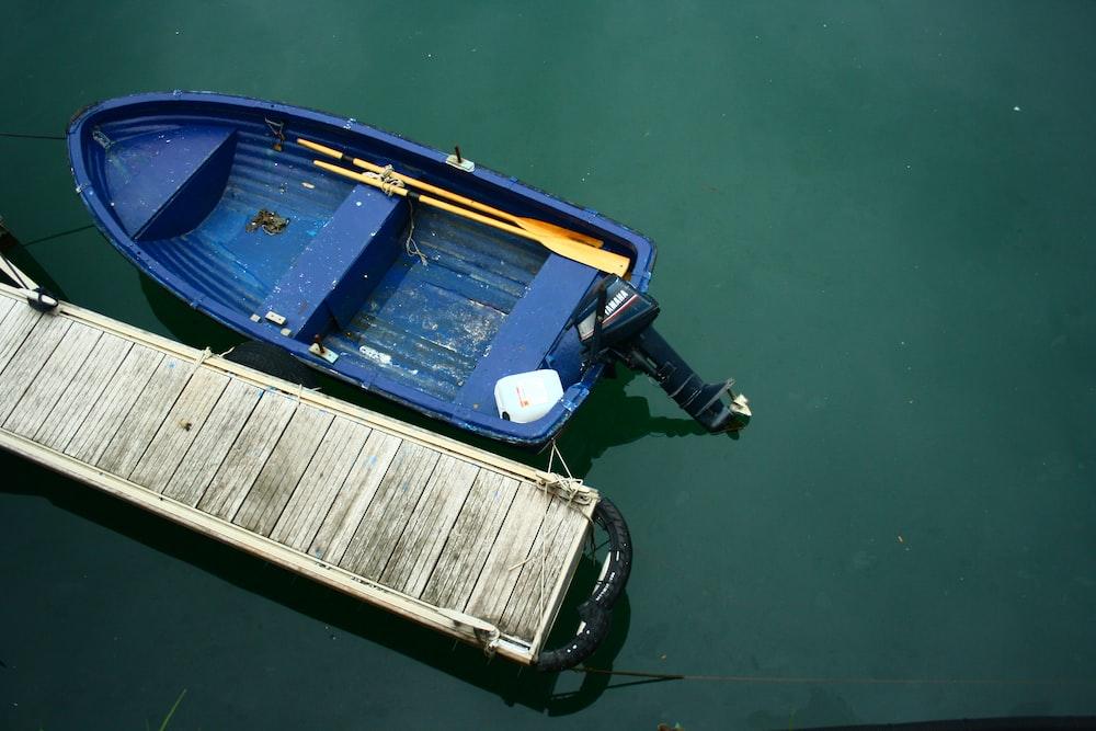 blue jon boat beside beige dock