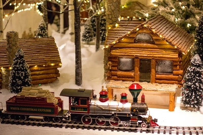 multicolored train toy near house gingerbread teams background