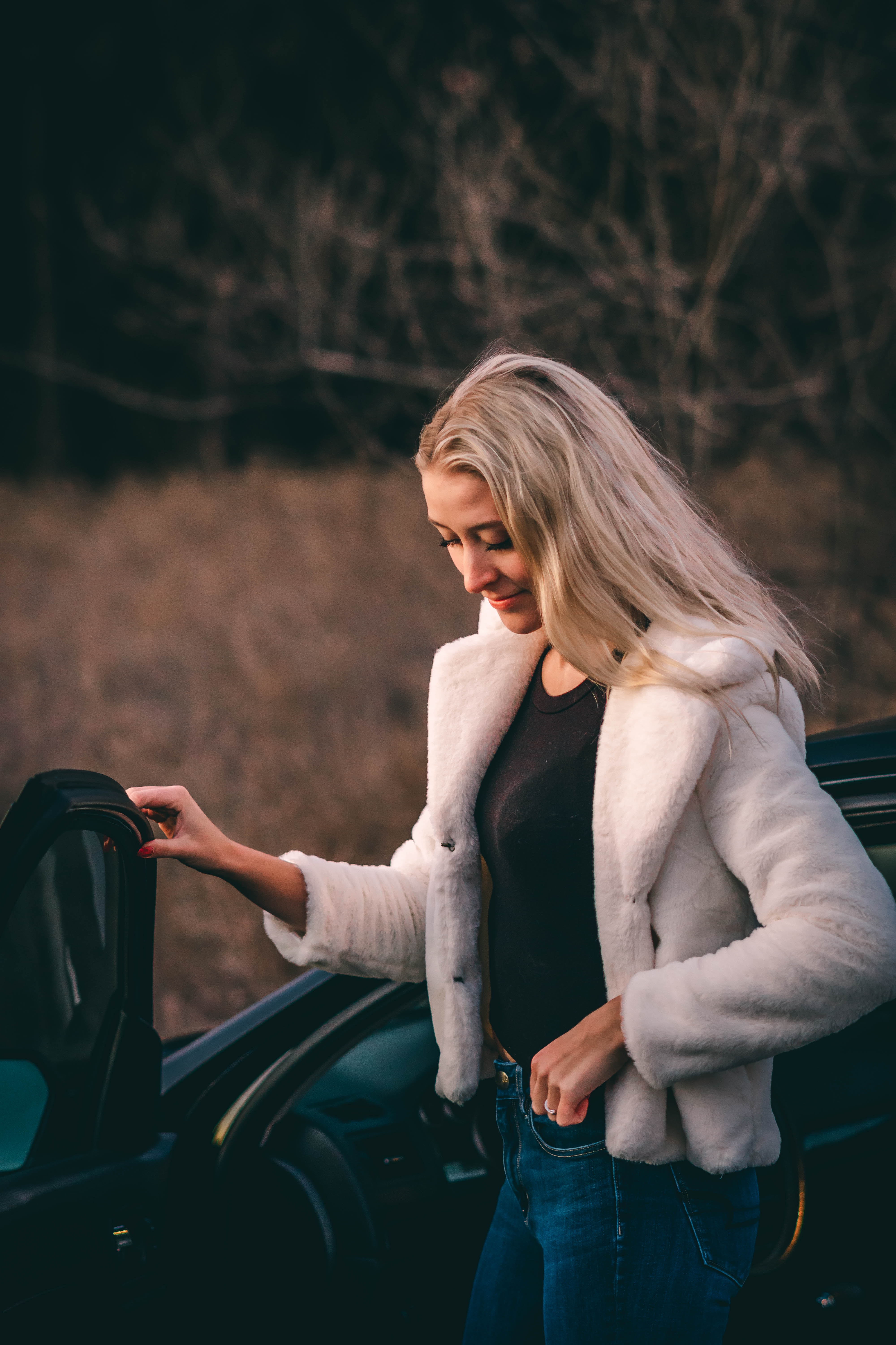 woman standing beside car near bare trees during golden hour