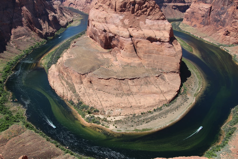 aerial photography of rock formation surrounded by river