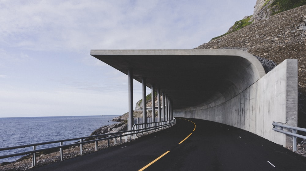 white road tunnel beside sea