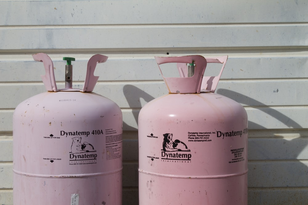 two pink Dynatemp 410 tanks on front of white wall