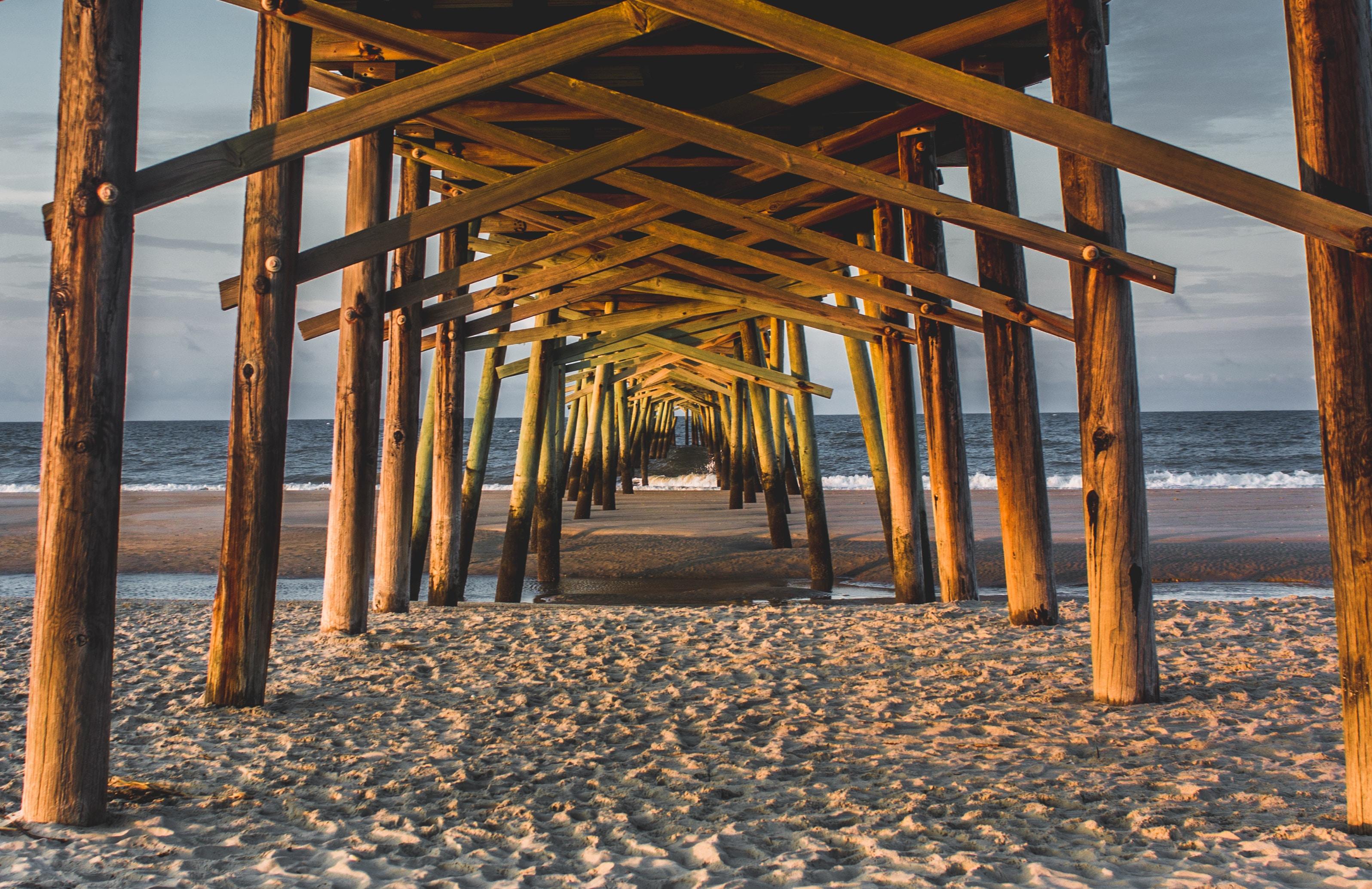 brown wooden walkway above gray sand