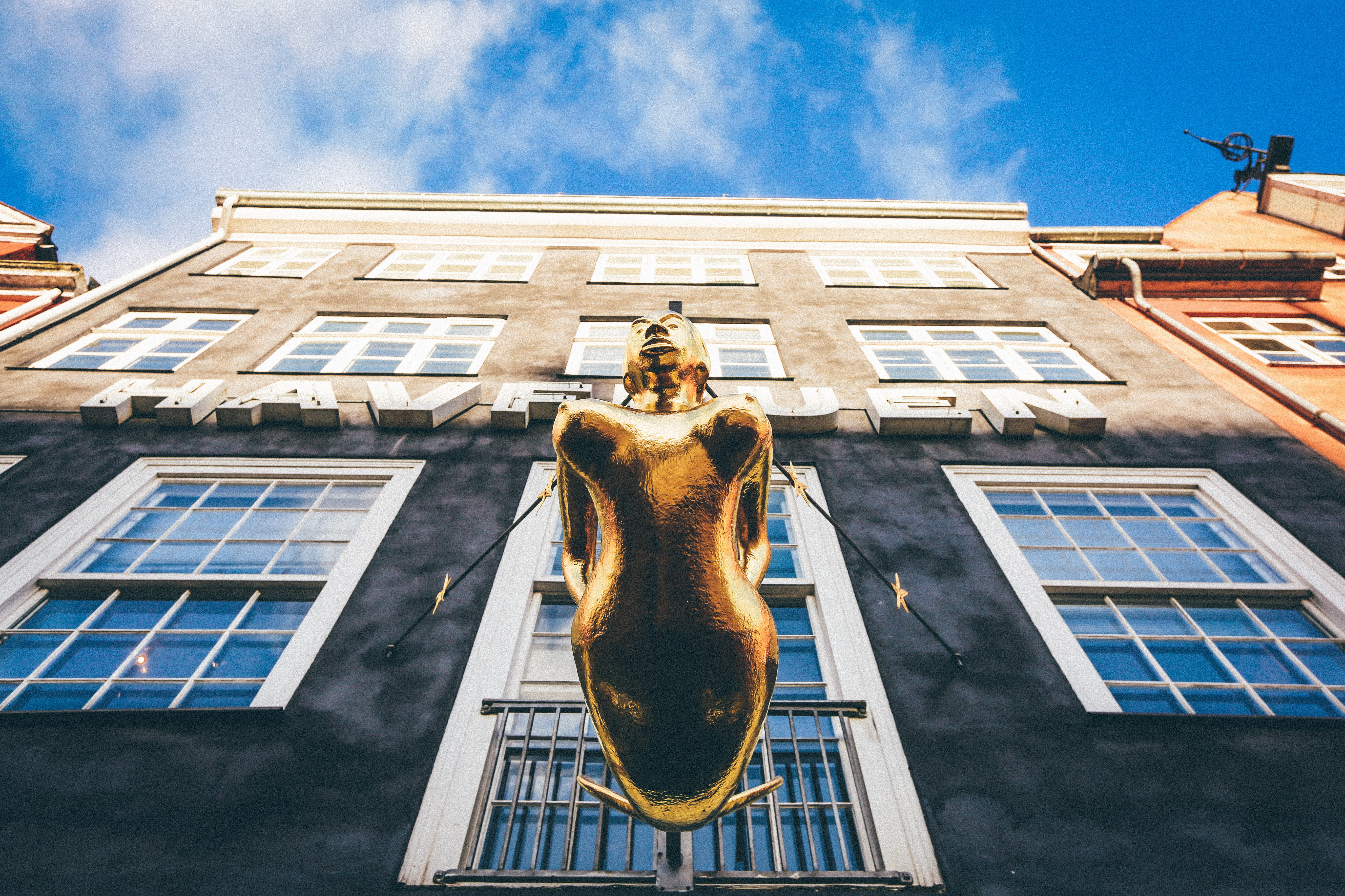 low angle photography of brown woman statue in front of building under white and blue building