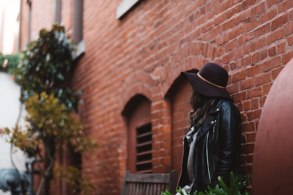 woman leaning against wall during daytime