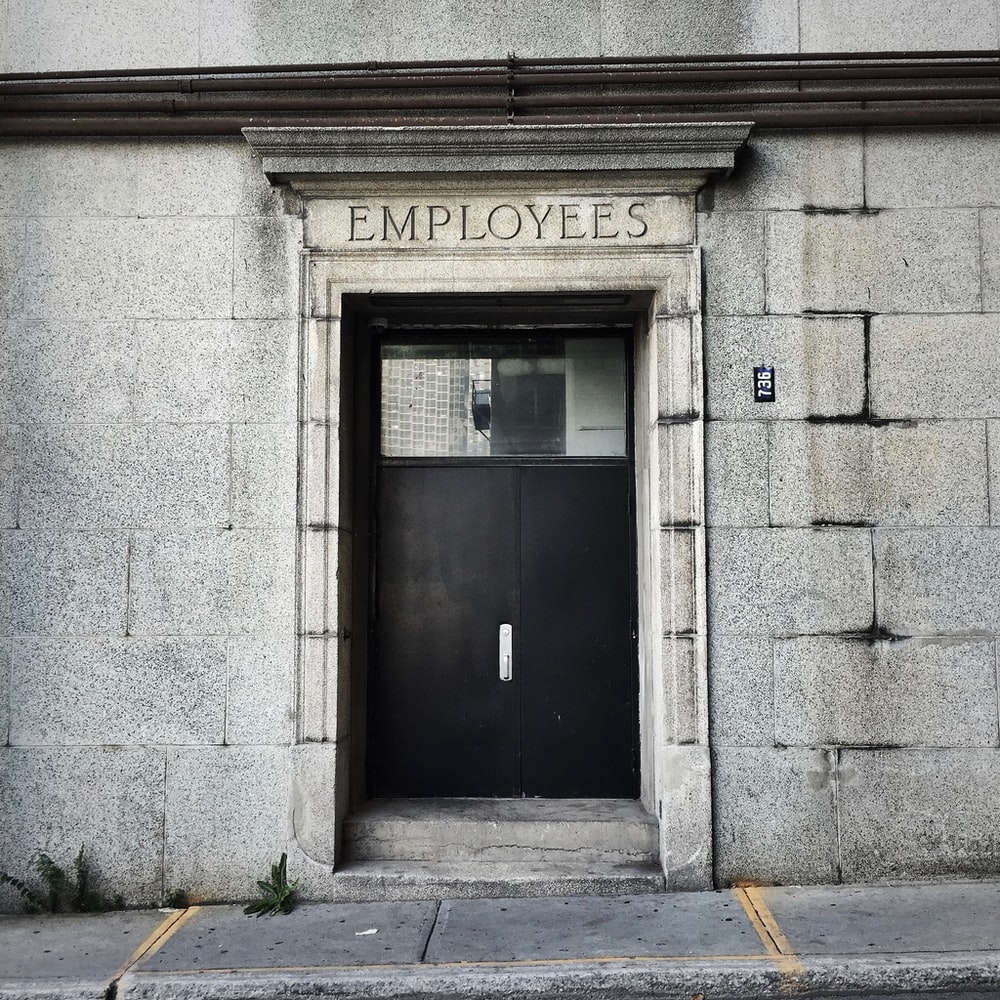 black wooden door with employee text overtop