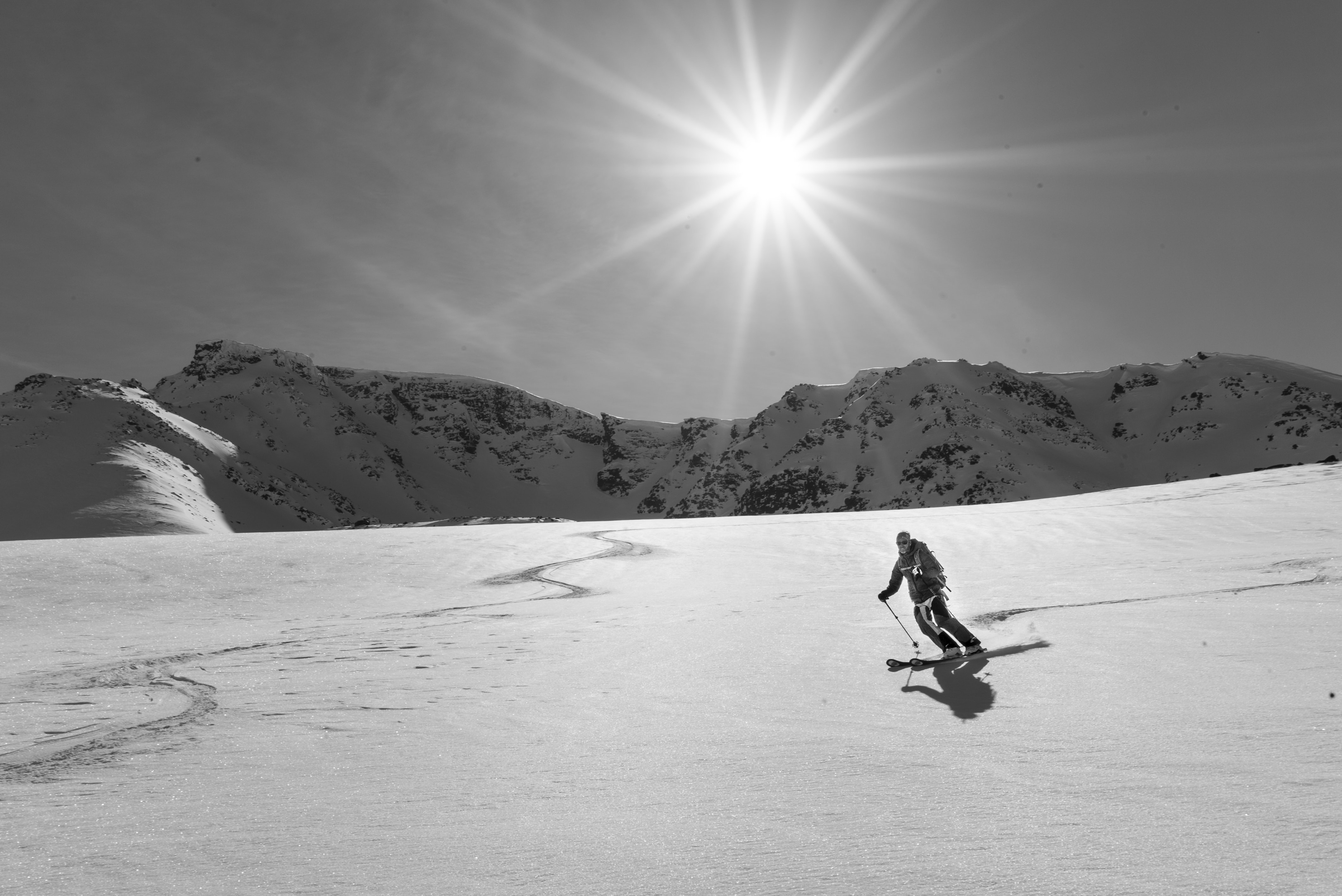 grayscale photography of person skiing on snowy mountain