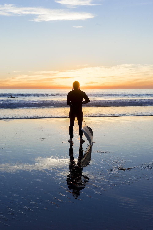 silhouette of man beside body of water