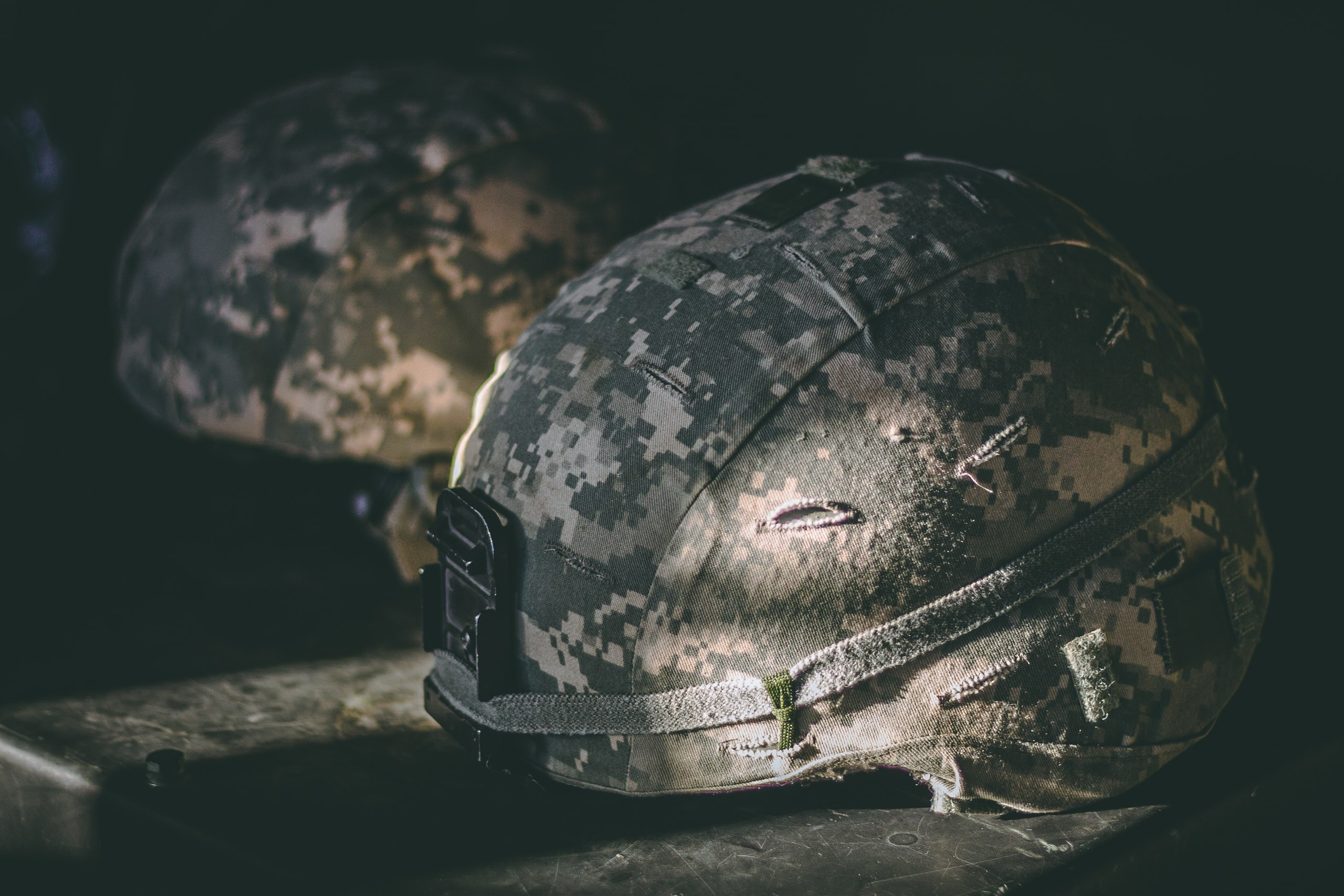gray and brown camouflage nutshell helmet on table