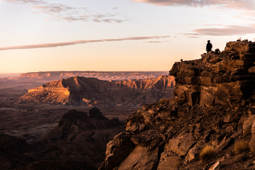 silhouette photo of man standing on top of cliff