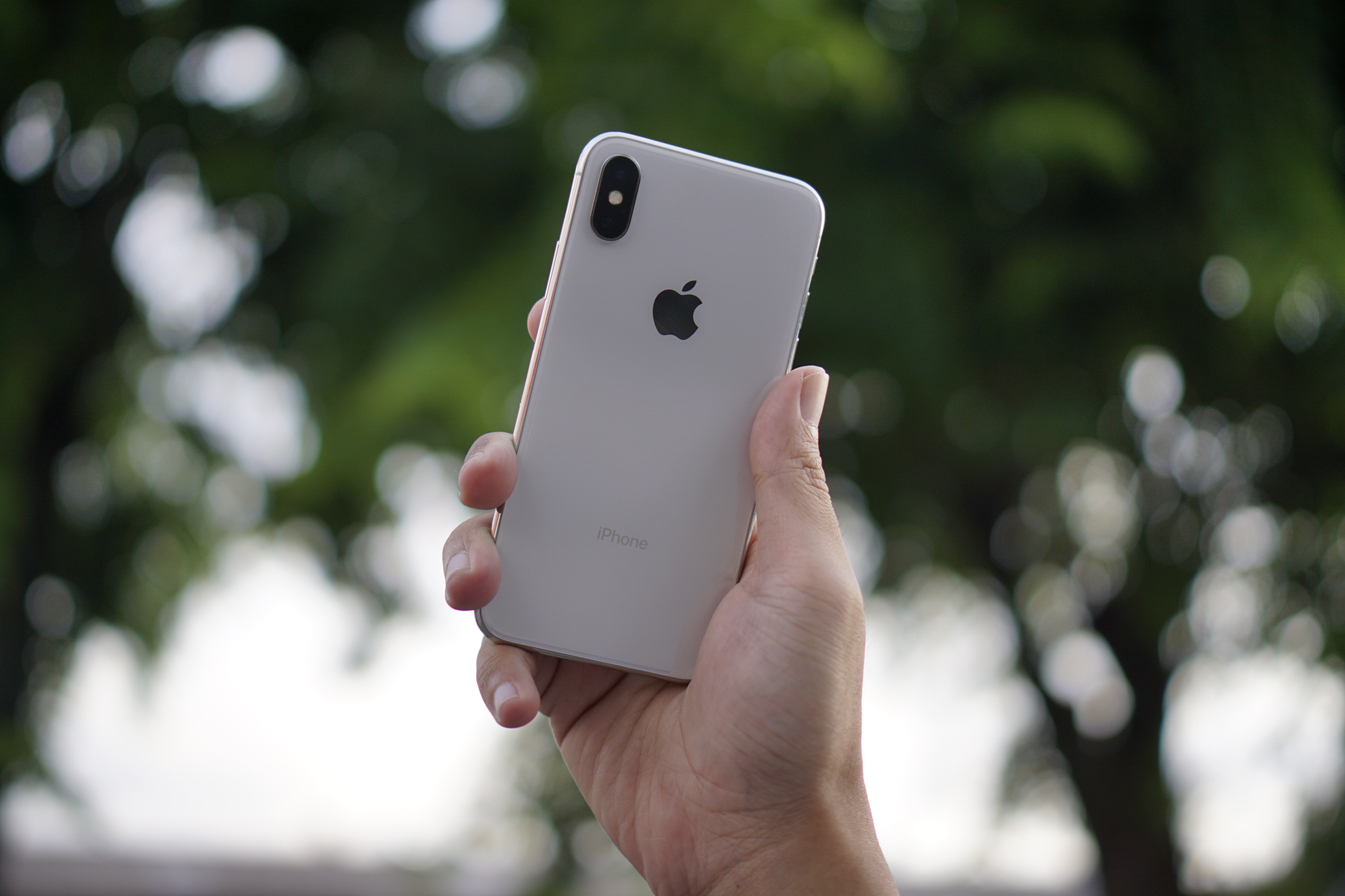 person holding silver iPhone X during daytime