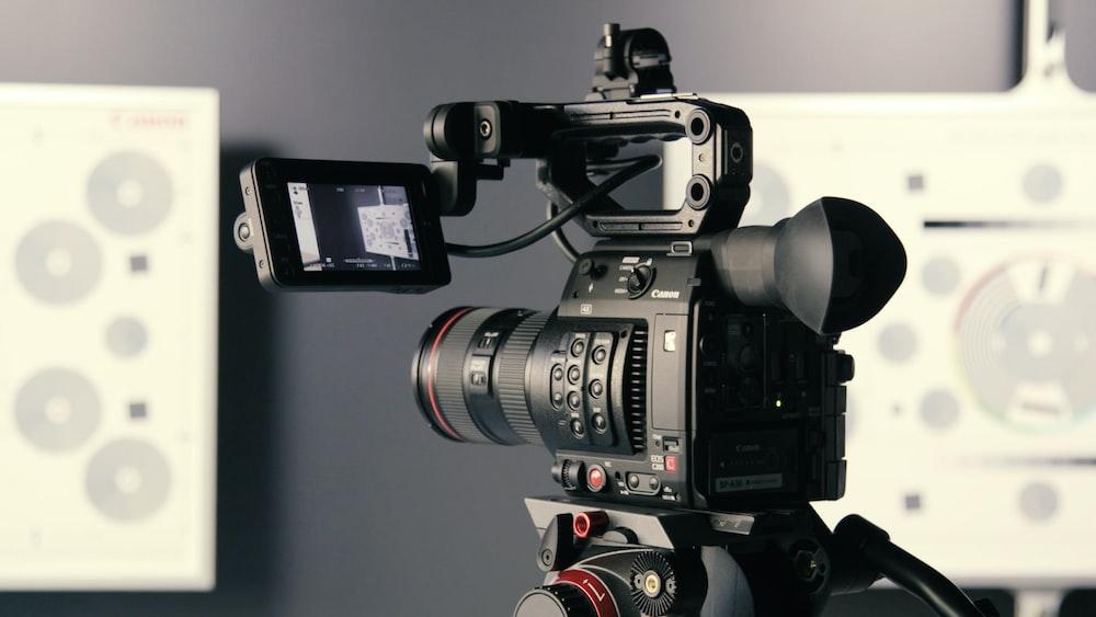 black DSLR camera with screen attachment