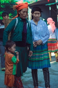 woman holding child beside woman wearing blue top