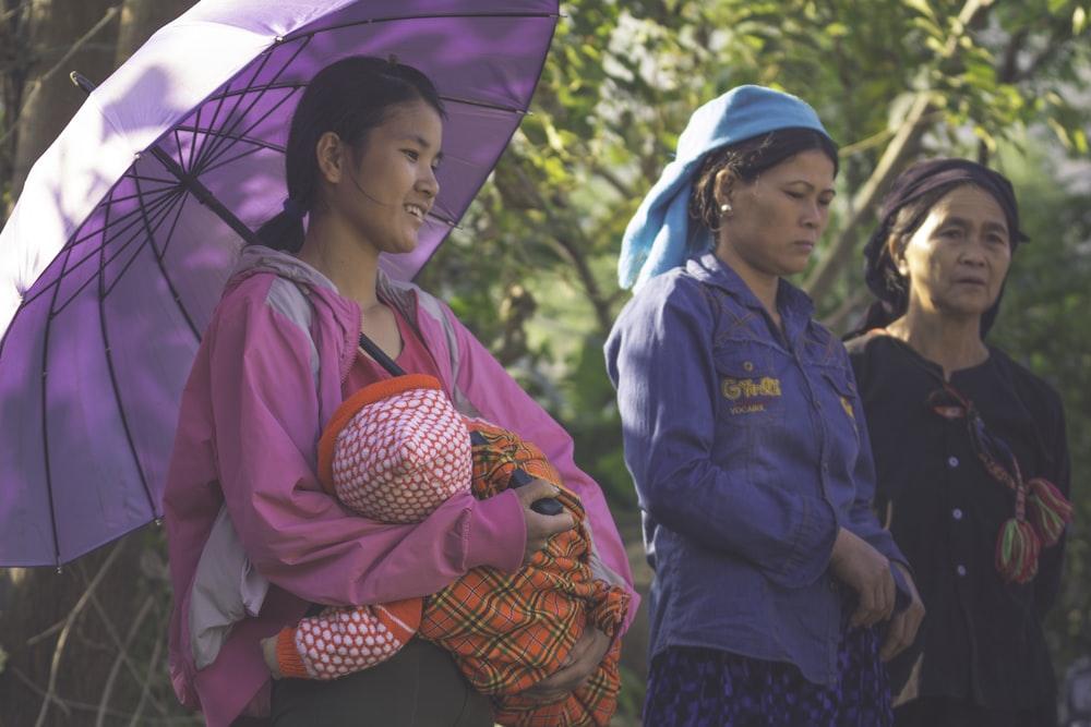 woman carrying baby under purple umbrella