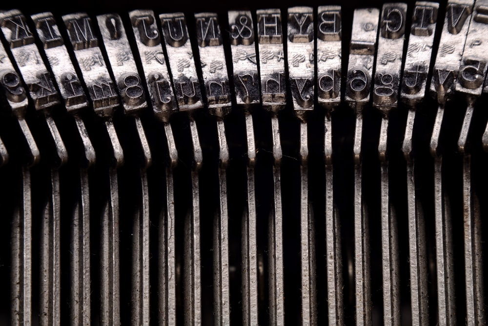 focus photography of silver typewriter pins
